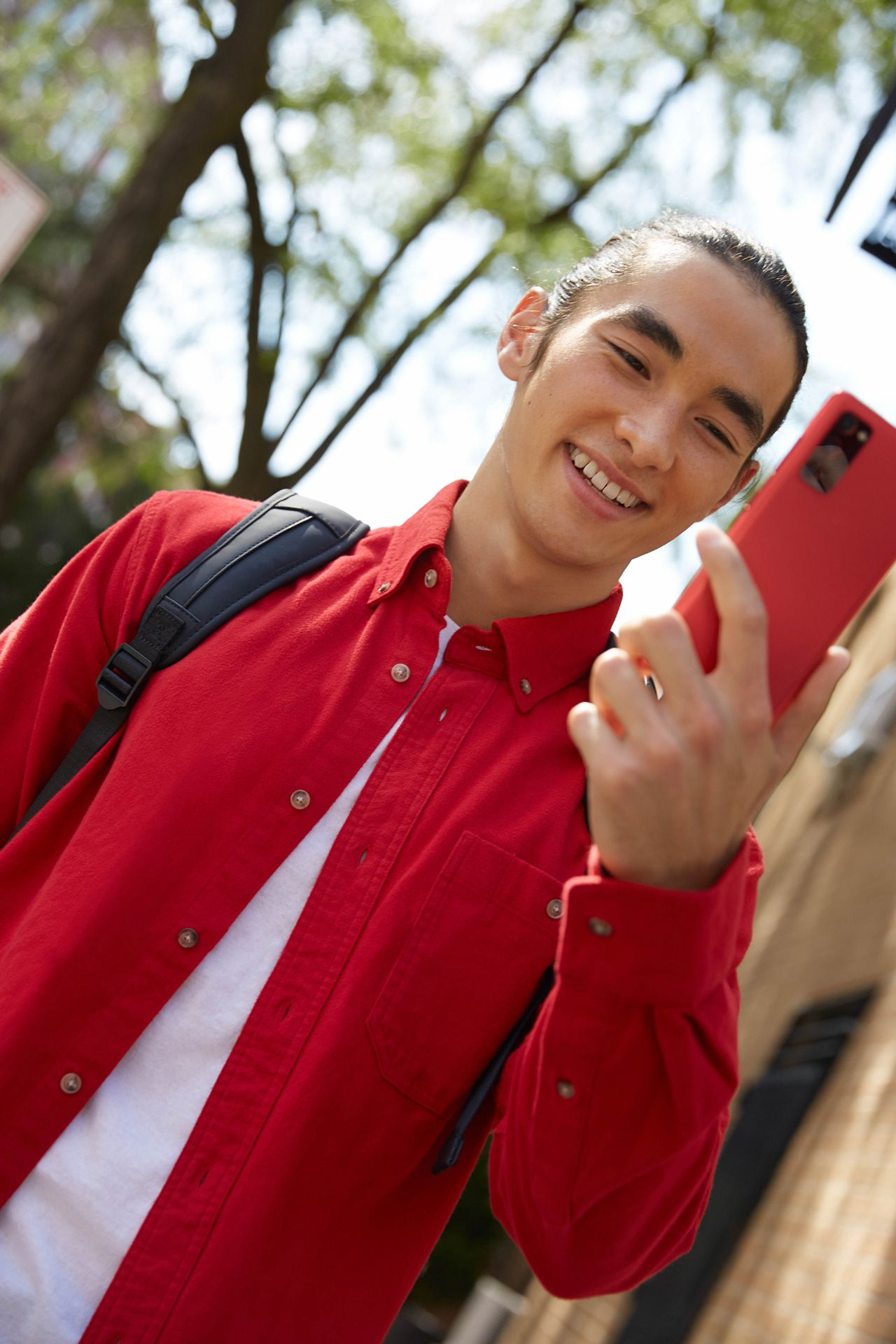 asian male model smiling looking at red smartphone wearing red shirt photographed by Oumayma B Tanfous for Samsung phone campaign