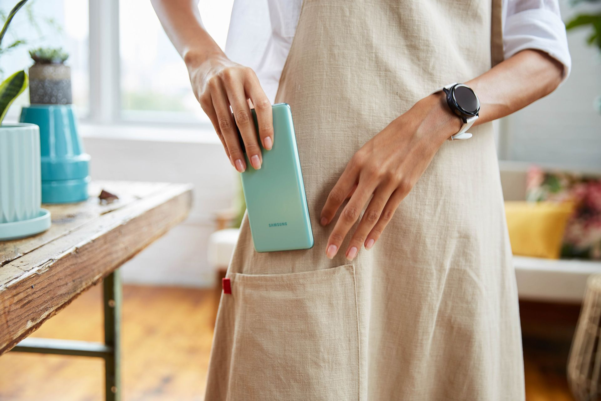 female model wearing beige apron and white shirt putting turquoise smartphone inside apron's pocket photographed by Oumayma B Tanfous for Samsung phone campaign