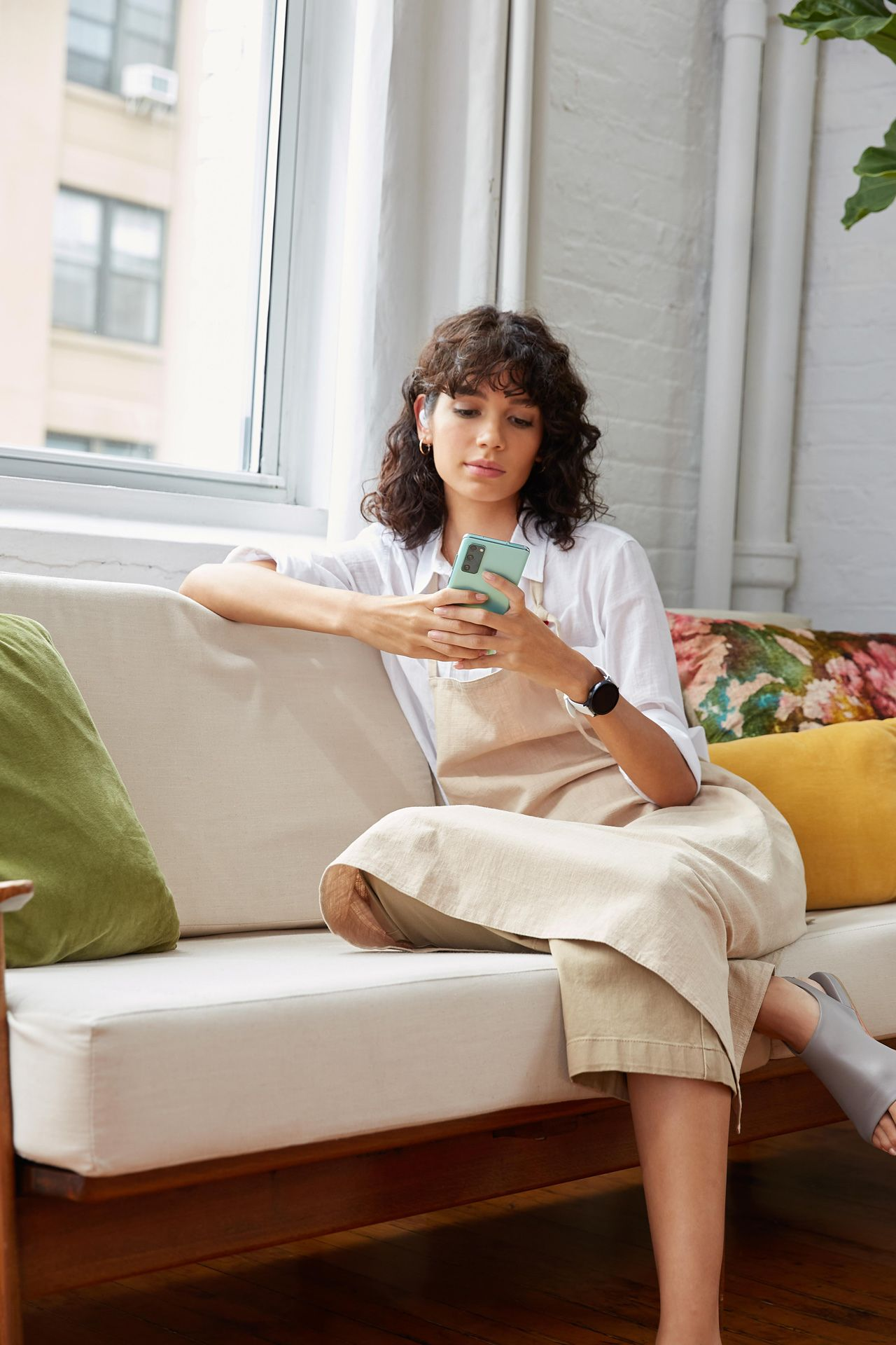 curly haired female model wearing beige apron and white shirt sitting on white couch typing on turquoise smartphone wearing wireless earpiece photographed by Oumayma B Tanfous for Samsung phone campaign