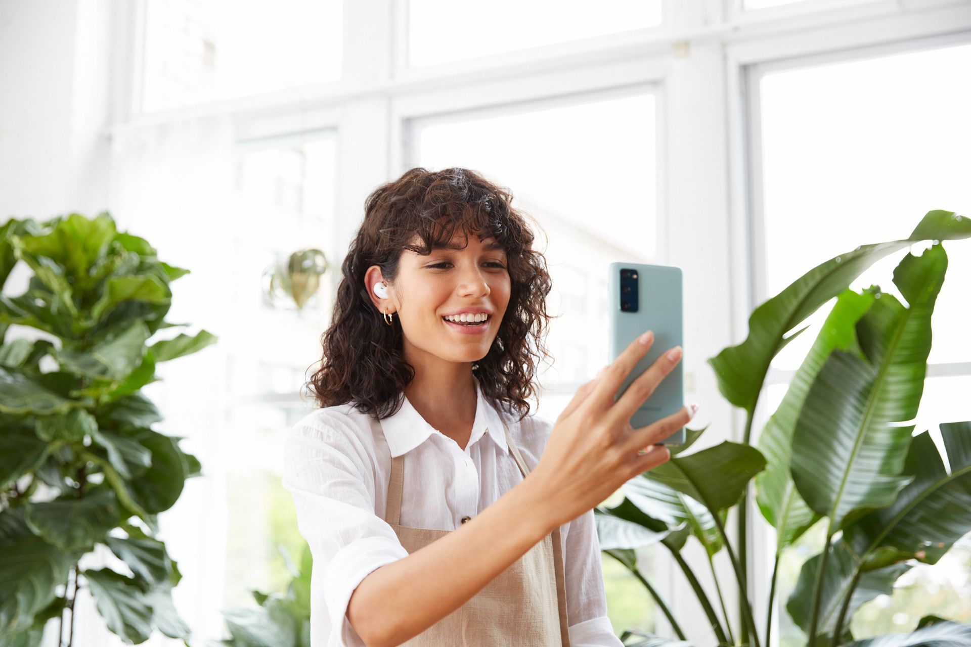 curly haired female model wearing beige apron and white shirt in nursery surrounded by plants talking to a turquoise smartphone wearing wireless earpiece photographed by Oumayma B Tanfous for Samsung phone campaign
