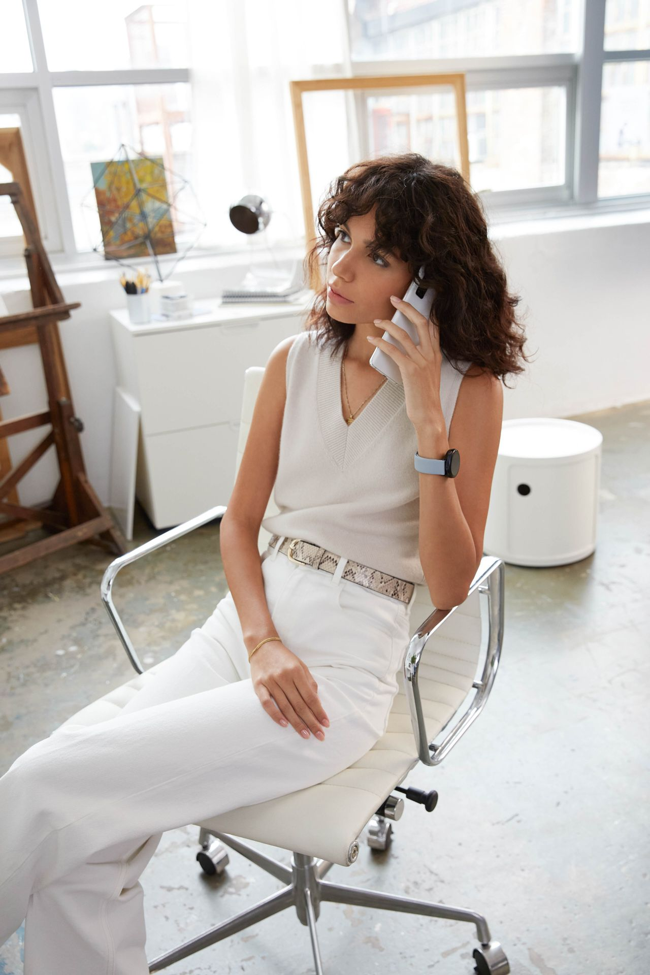 curly haired female model wearing white pants and white blouse sitting on white office chair talking on a white smartphone photographed by Oumayma B Tanfous for Samsung phone campaign