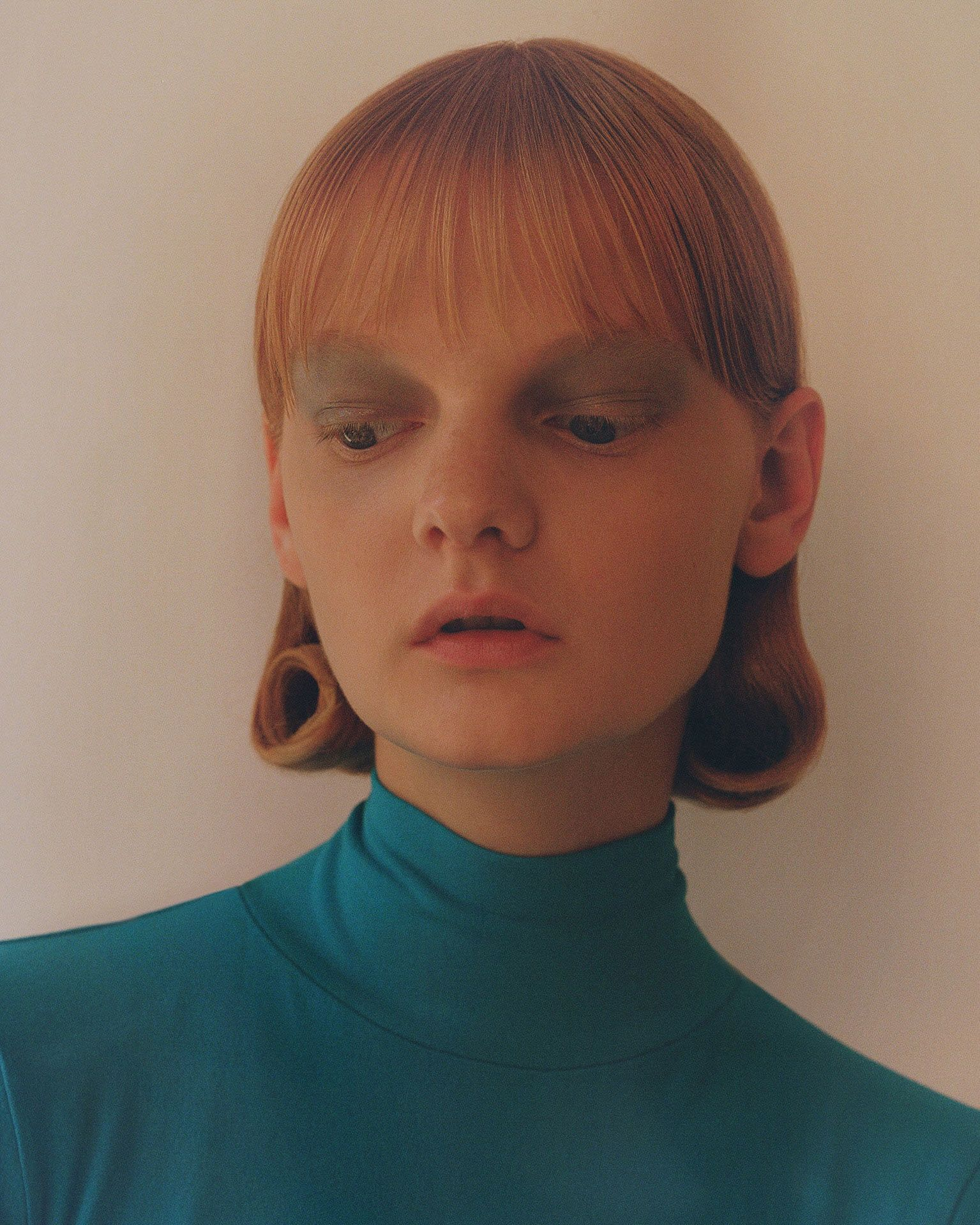 redhead female model wearing turquoise makeup and turquoise turtleneck looking down photographed by Oumayma B Tanfous for Moncler as a story for Document Journal magazine