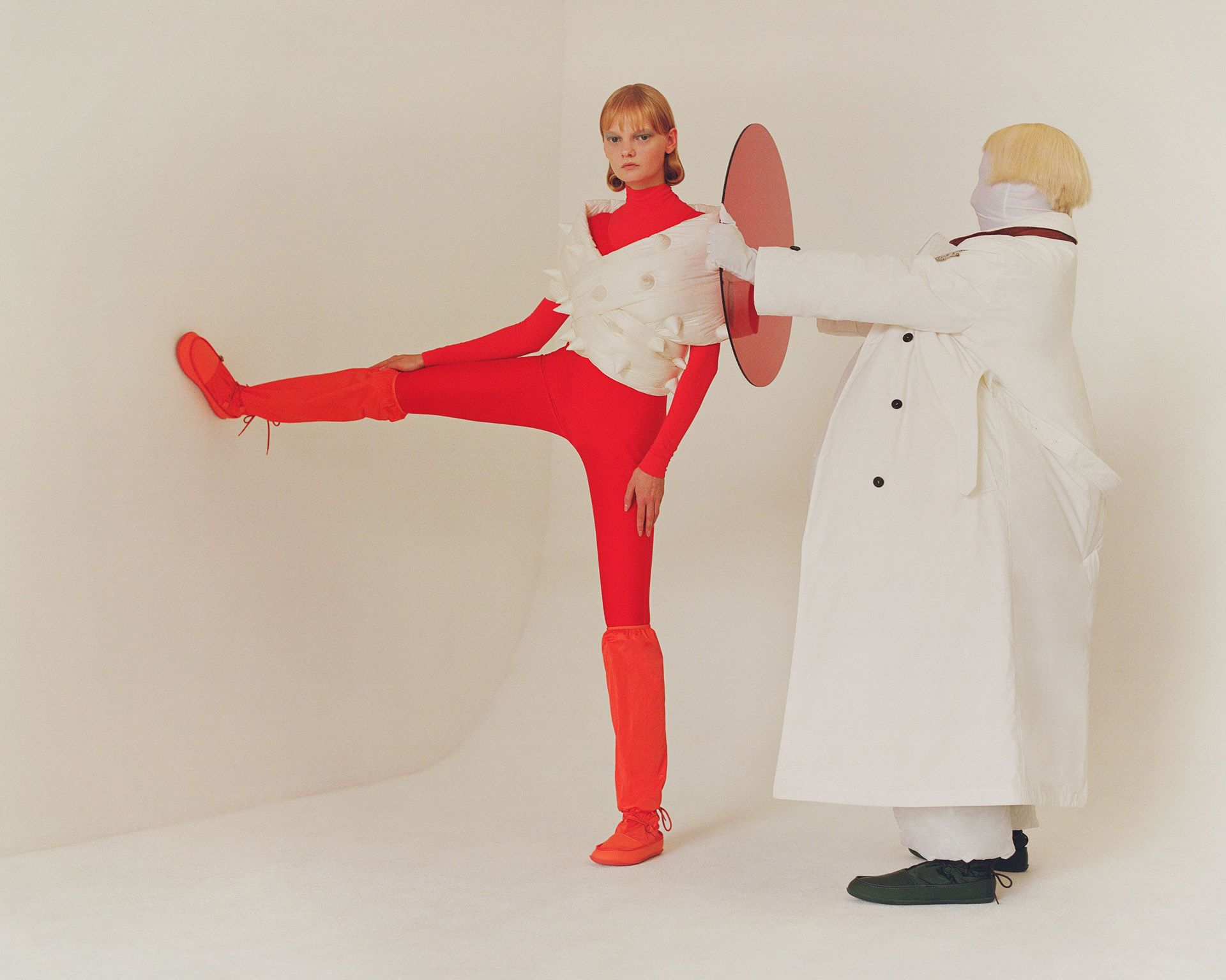 redhead female model wearing red boots red overalls and white puffy spiked coat photographed by Oumayma B Tanfous for Moncler as a story for Document Journal magazine