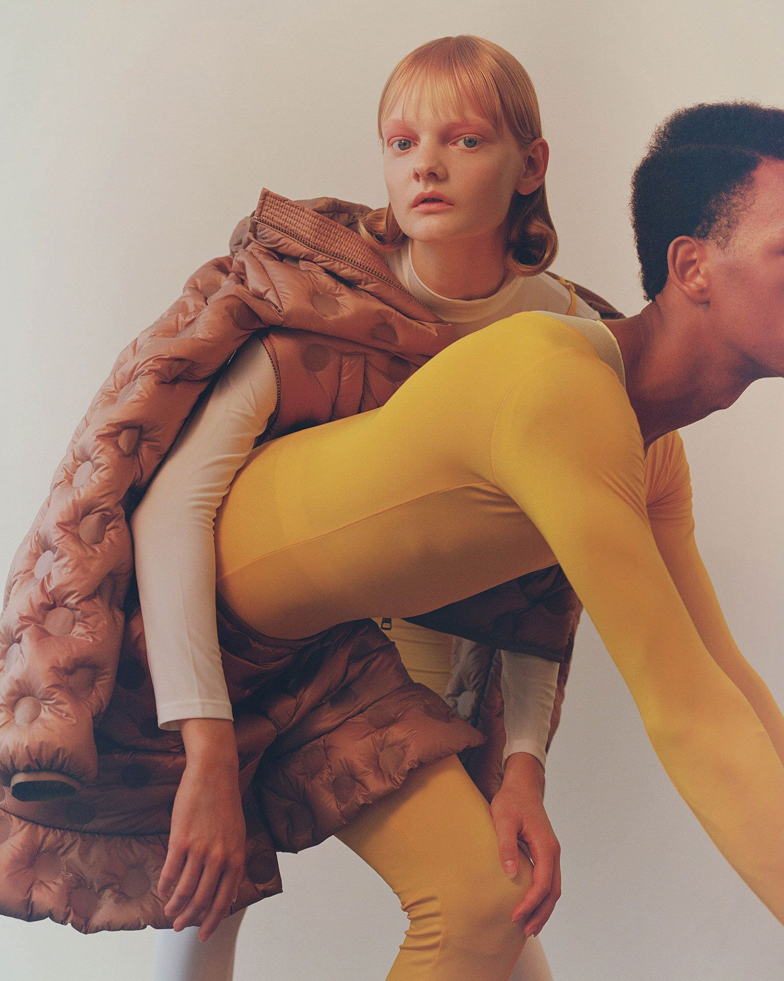 redhead female model wearing white bodysuit and black male model wearing yellow bodysuit both wearing the same brown puffy coat photographed by Oumayma B Tanfous for Moncler as a story for Document Journal magazine