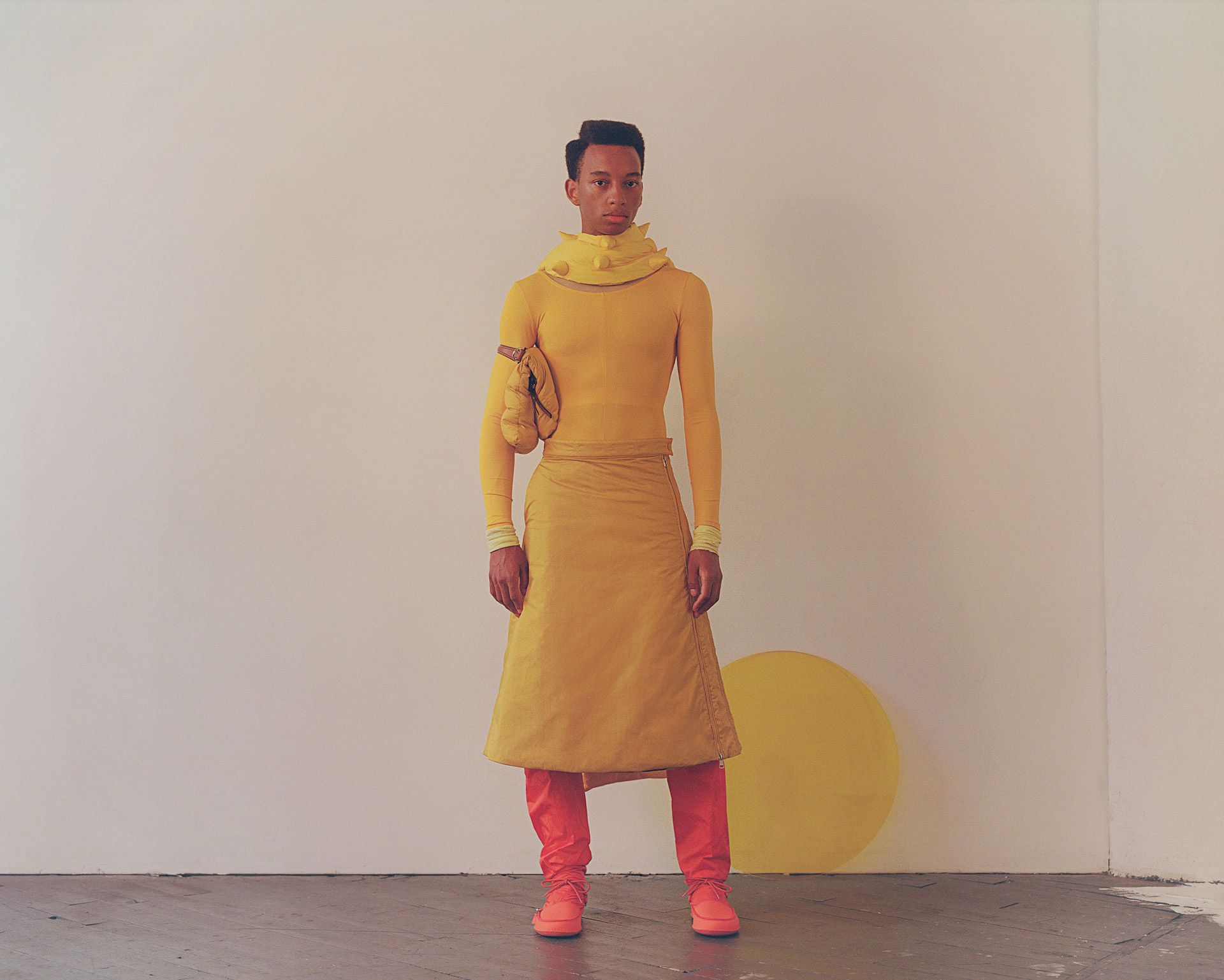 black male model standing in studio looking at camera wearing red boots yellow skirt yellow long-sleeved shirt and small yellow puffy spiked scarf with yellow acrylic circle in the background photographed by Oumayma B Tanfous for Moncler as a story for Document Journal magazine