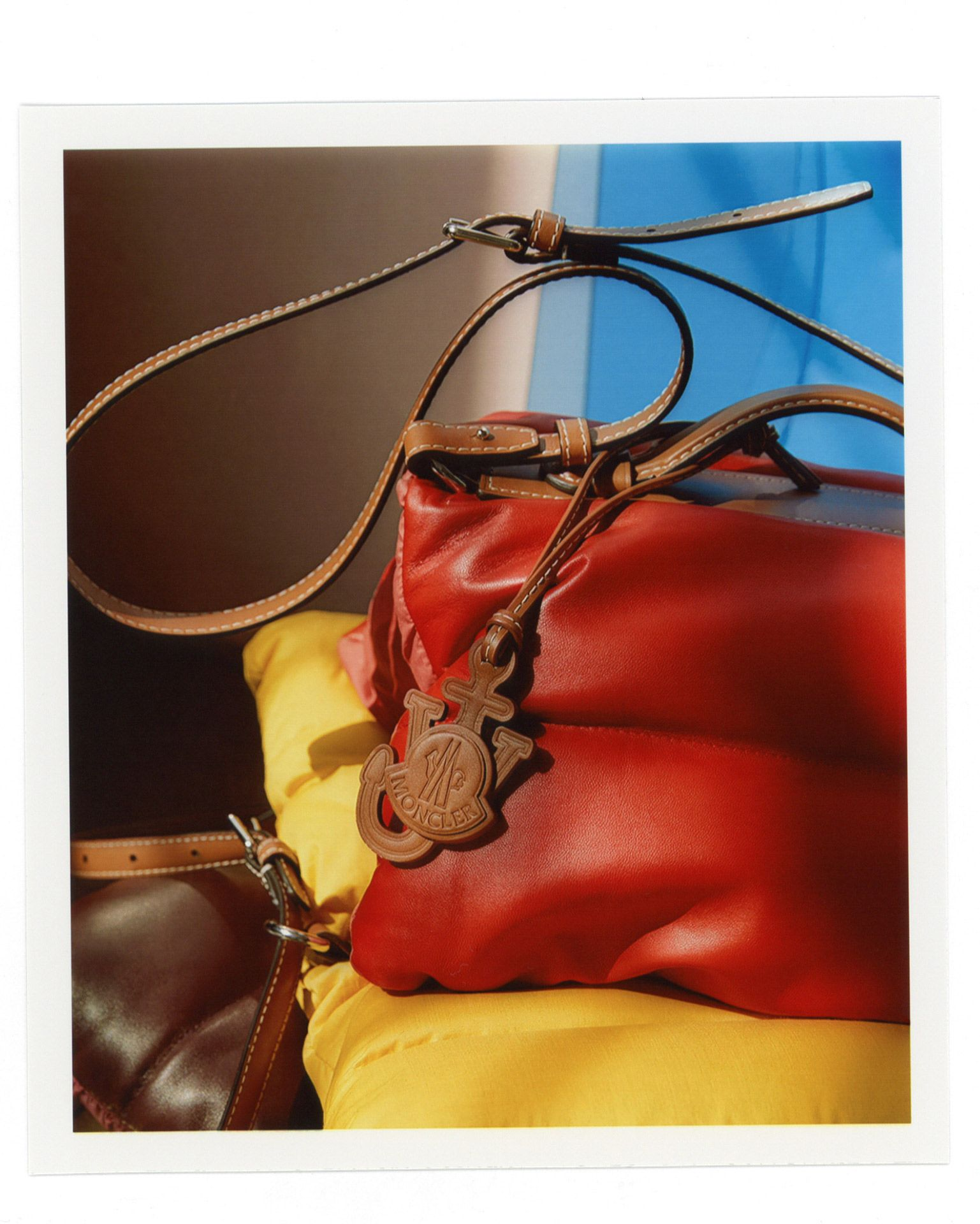 red leather bag resting on puffy yellow coat photographed by Oumayma B Tanfous for Moncler as a story for Document Journal magazine