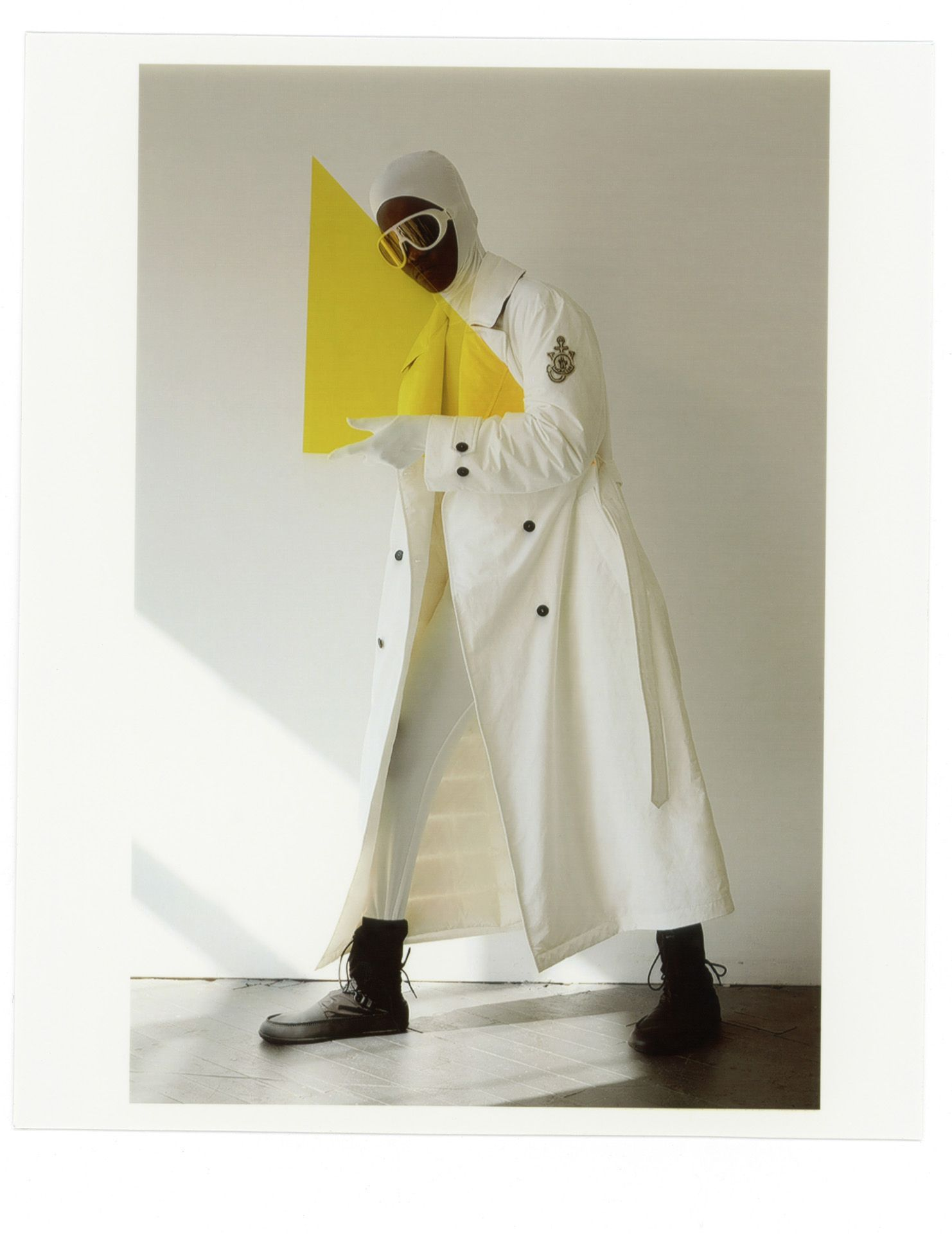 black female model wearing long white coat white sunglasses and white balaclava holding yellow acrylic triangle with one arm photographed by Oumayma B Tanfous for Moncler as a story for Document Journal magazine