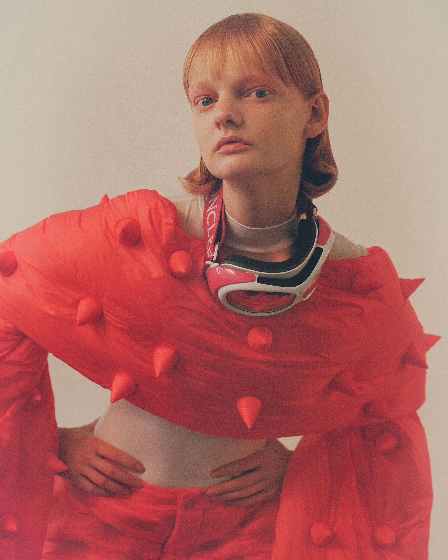 redhead model with hands on hips looking at camera wearing puffy red pants and red puffy spiked long scarf photographed by Oumayma B Tanfous for Moncler as a story for Document Journal magazine