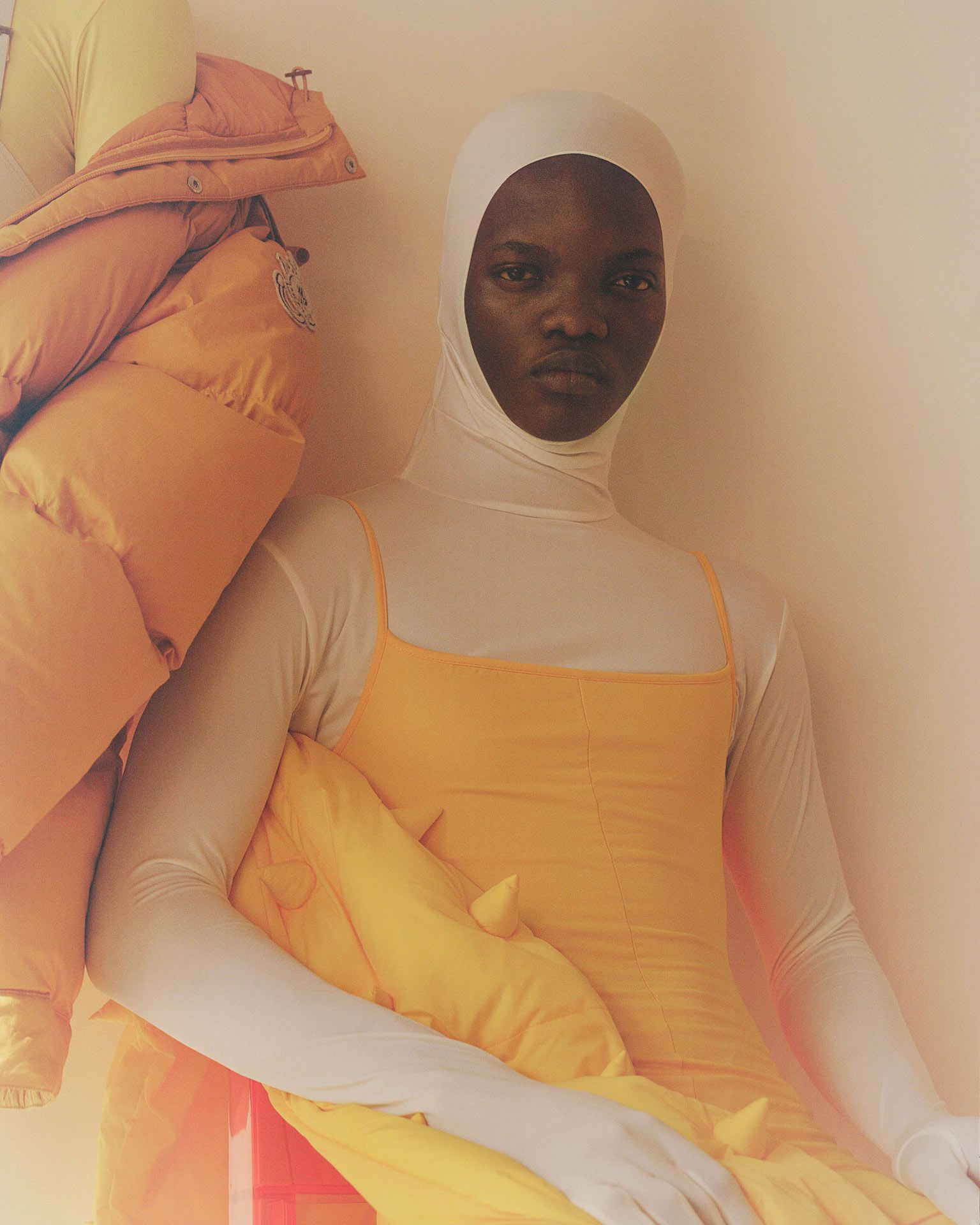 black model sitting on chair looking at camera wearing white bodysuit with a yellow spaghetti stripes top on top photographed by Oumayma B Tanfous for Moncler as a story for Document Journal magazine