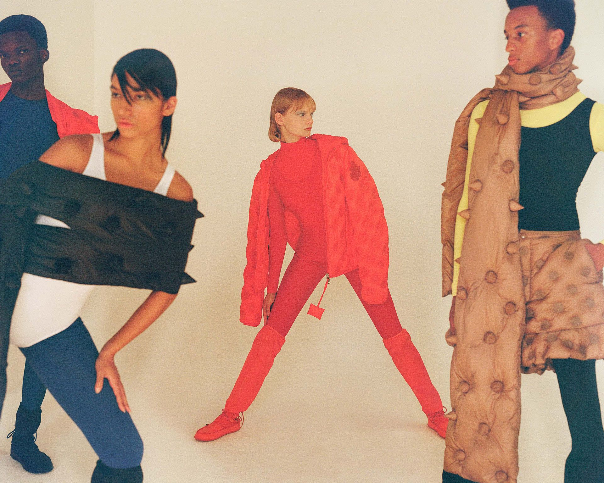 group of four models posing differently wearing different colors of puffy spiked coats photographed by Oumayma B Tanfous for Moncler as a story for Document Journal magazine