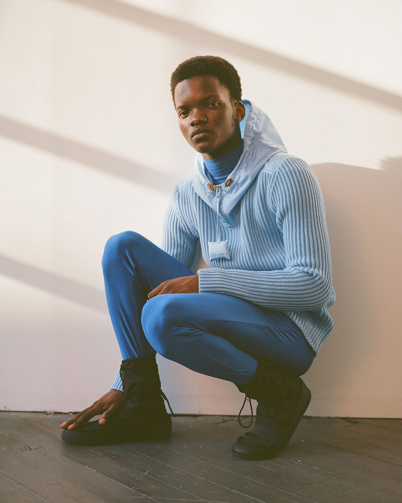 black male model crouching on the ground looking at camera wearing blue overalls and powder blue sweater photographed by Oumayma B Tanfous for Moncler as a story for Document Journal magazine