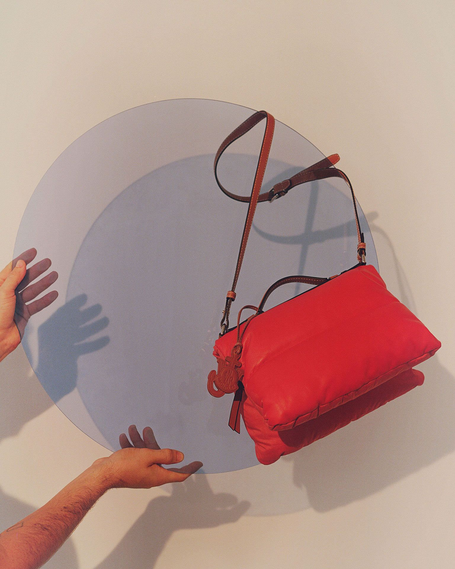 red leather bag hooked on light blue acrylic circle held by two hands in the air photographed by Oumayma B Tanfous for Moncler as a story for Document Journal magazine