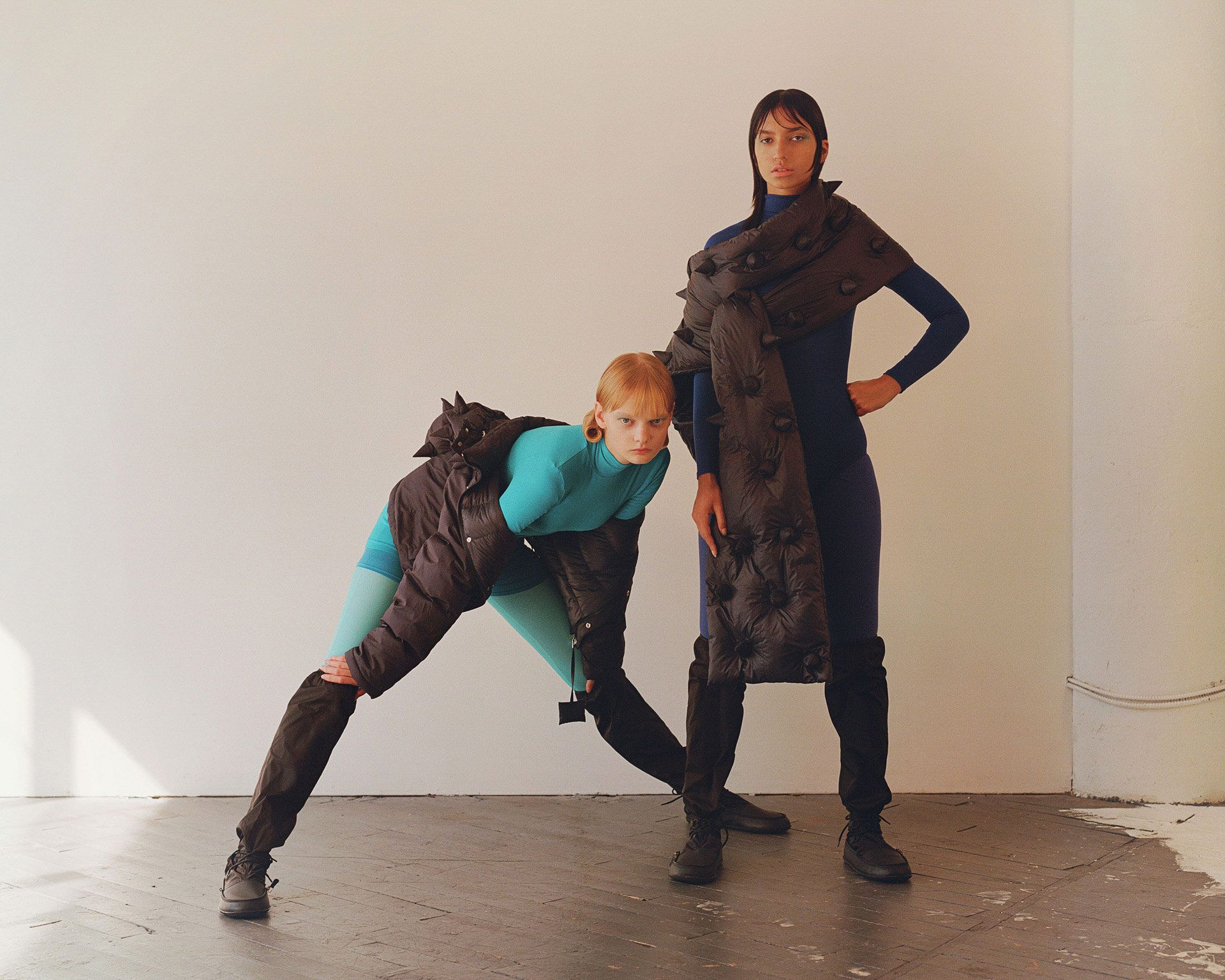 redhead female model wearing turquoise overall and black puffy spiked coat next to black haired model wearing dark blue overall and black puffy spiked scarf photographed by Oumayma B Tanfous for Moncler as a story for Document Journal magazine