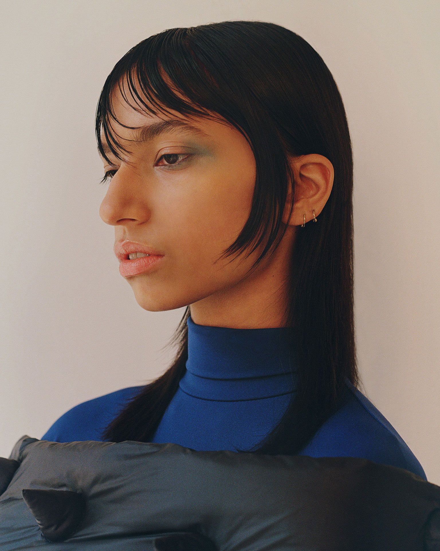 black haired female model wearing turquoise makeup blue turtleneck and black puffy spiked coat photographed by Oumayma B Tanfous for Moncler as a story for Document Journal magazine