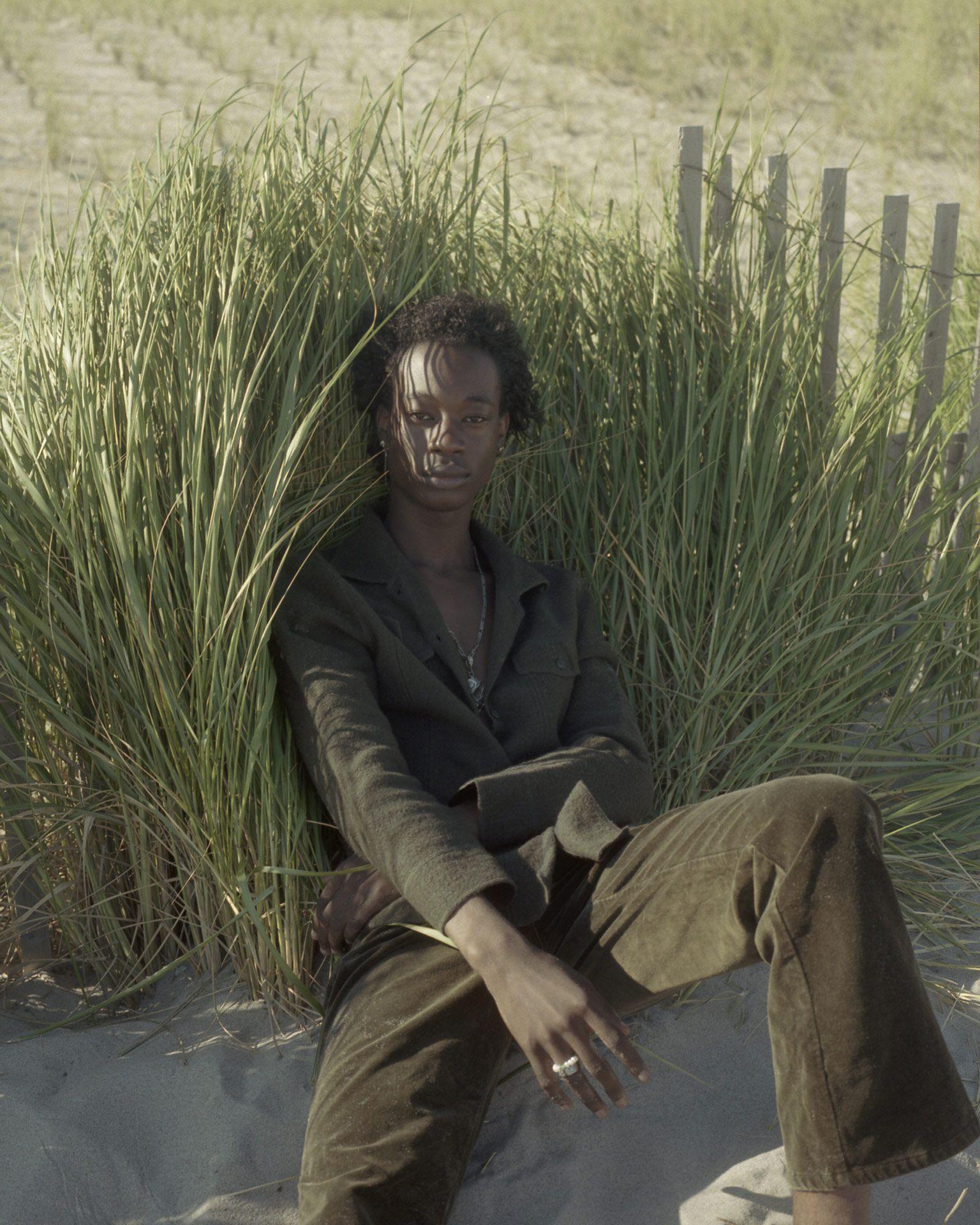 homme noir assis dans le sable le dos contre des herbes hautes regardant la caméra par Oumayma B. Tanfous pour DAZED