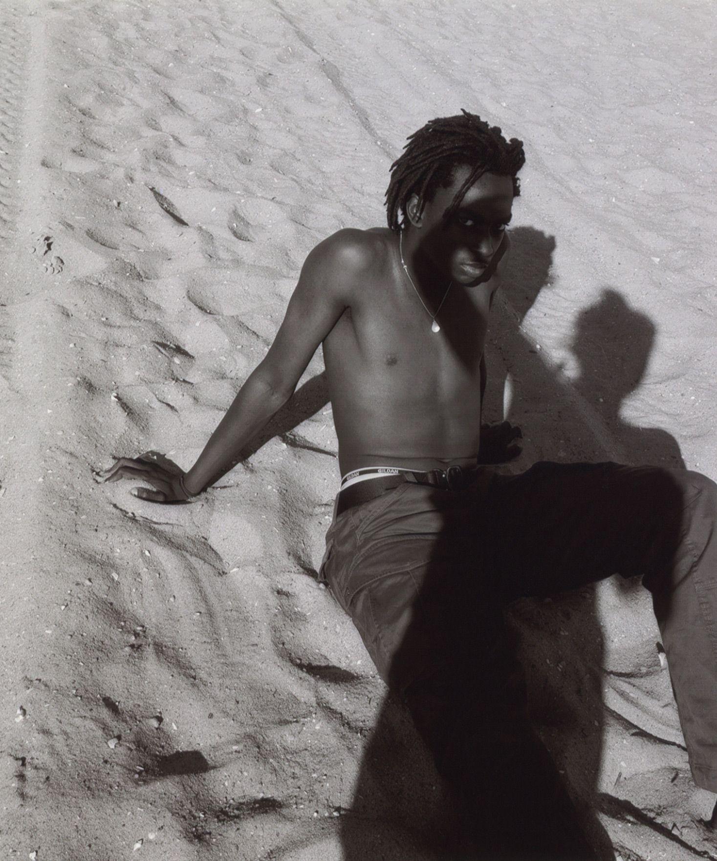 homme noir assis dans le sable penché en arrière et se soutenant avec ses mains l'ombre de la photographe sur lui par Oumayma B. Tanfous pour DAZED
