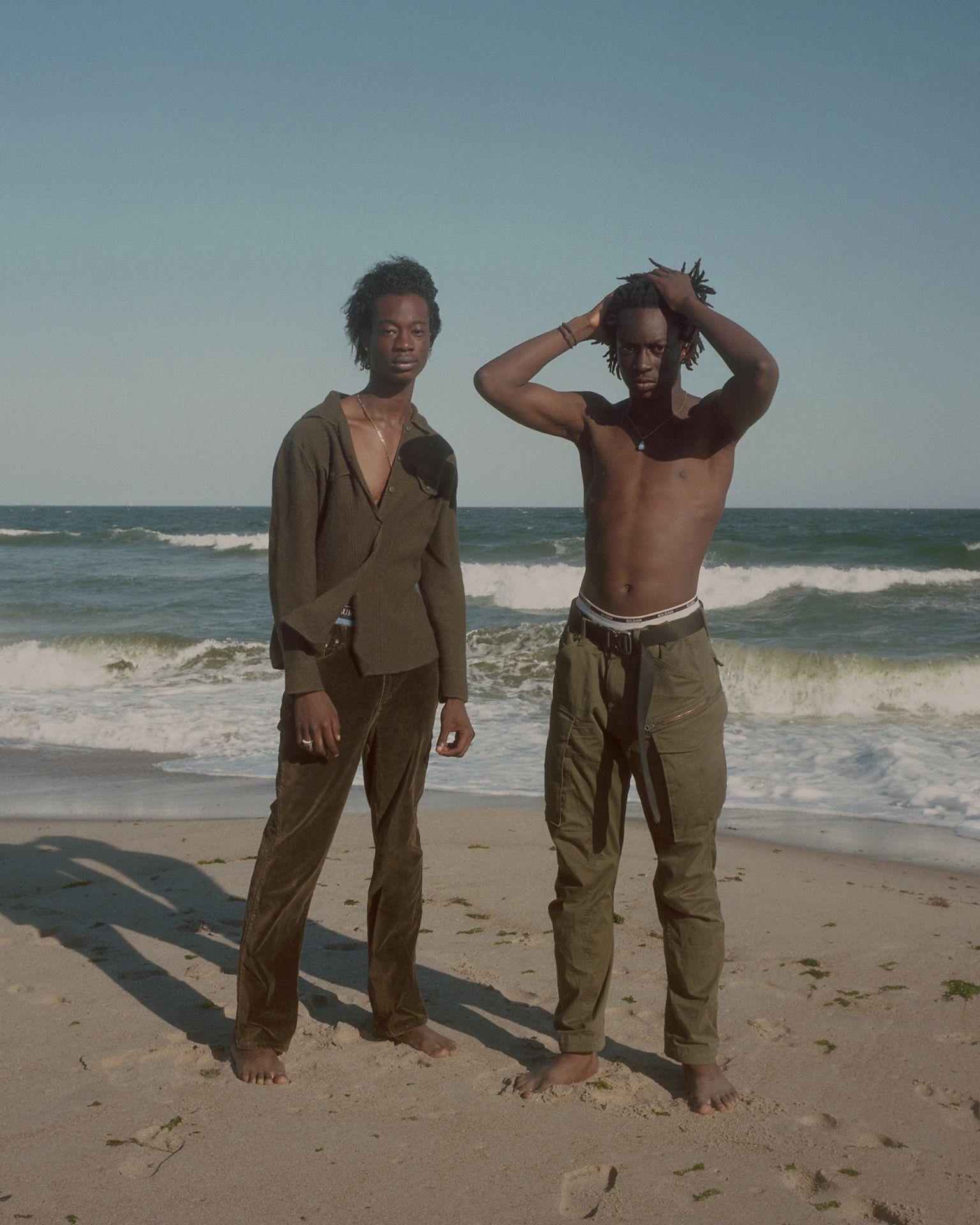 deux hommes noirs posant sur la plage debout l'un deux se touchant les cheveux les vagues s'écrasant derrière eux par Oumayma B. Tanfous pour DAZED