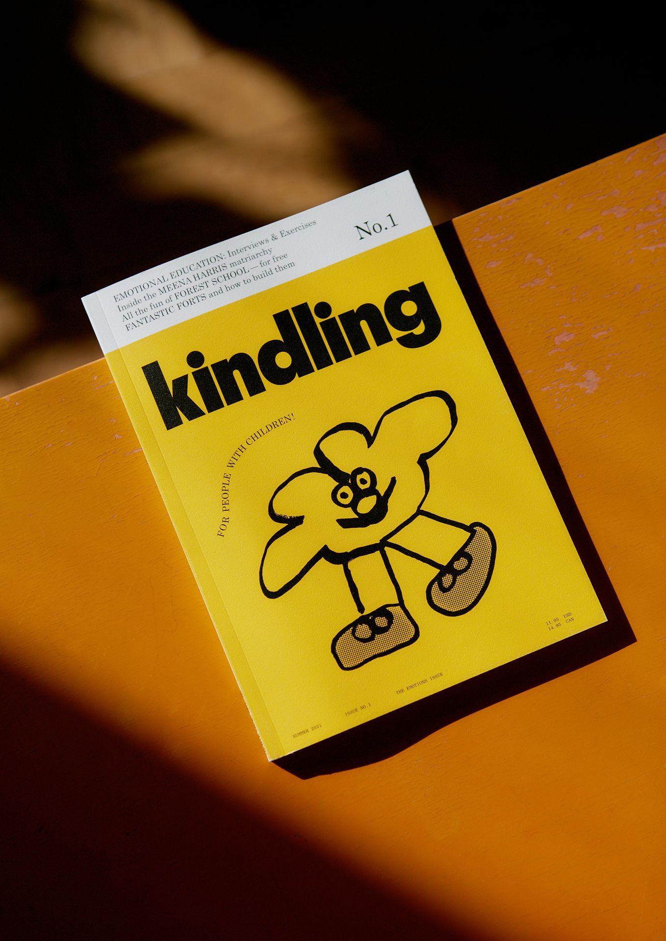 Photo du magazine Kindling avec une couverture jaune et un dessin noir par un enfant sur une table orange.