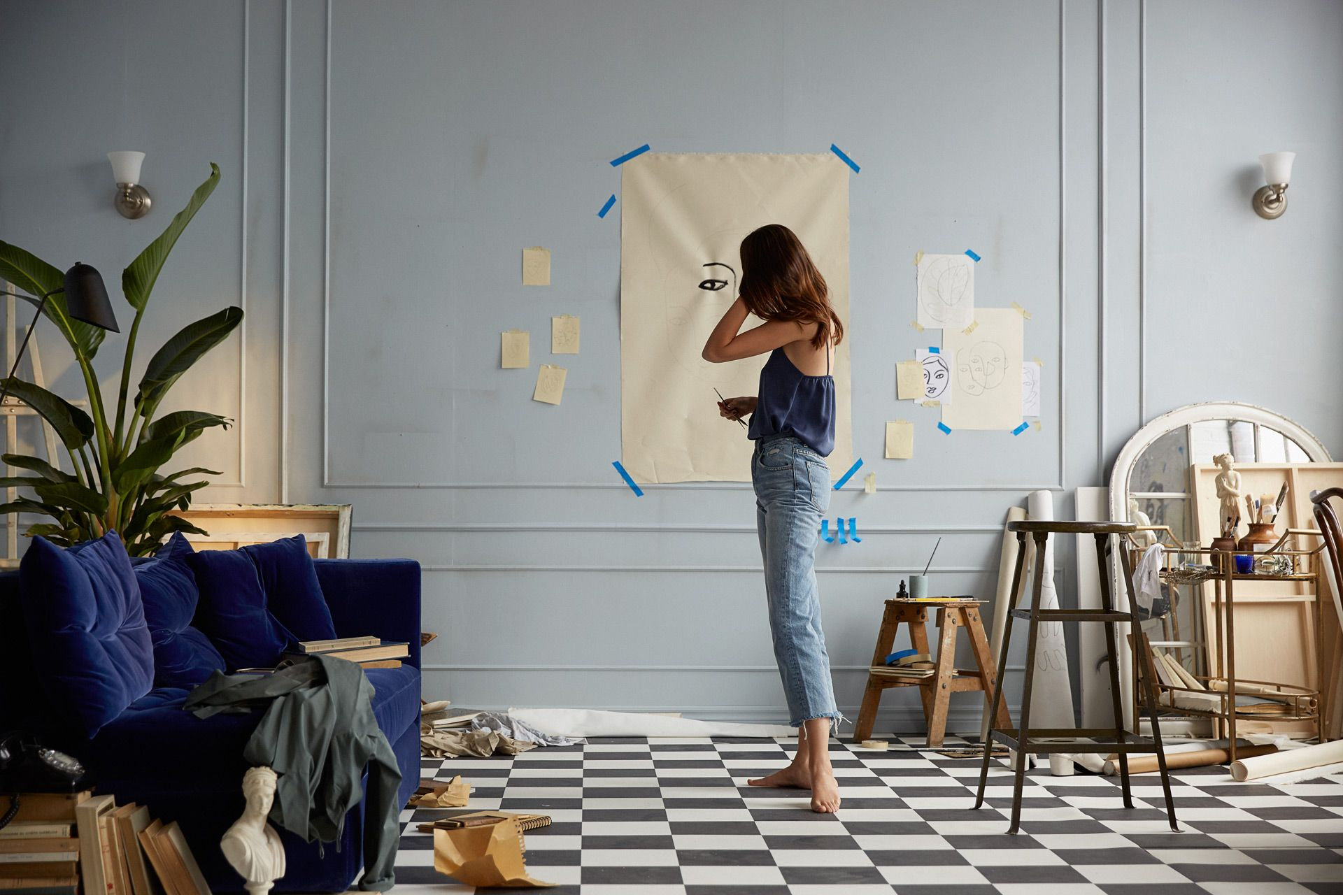 white woman model bare foot drawing on paper on the wall playing with her hair by Oumayma B Tanfous for Lancôme