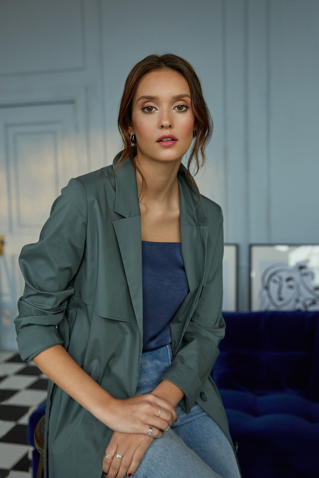white woman model sitting on high wood stool wearing dark blue-green trench coat looking at camera by Oumayma B Tanfous for Lancôme