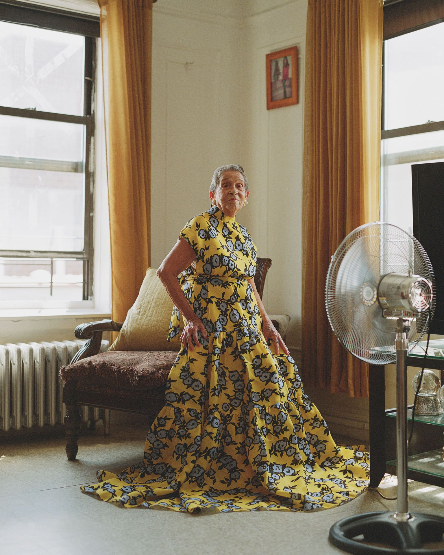 portrait of Altagracia de Pena sitting on an armchair wearing a long yellow dress by Oumayma B. Tanfous for Phosphenes Magazine