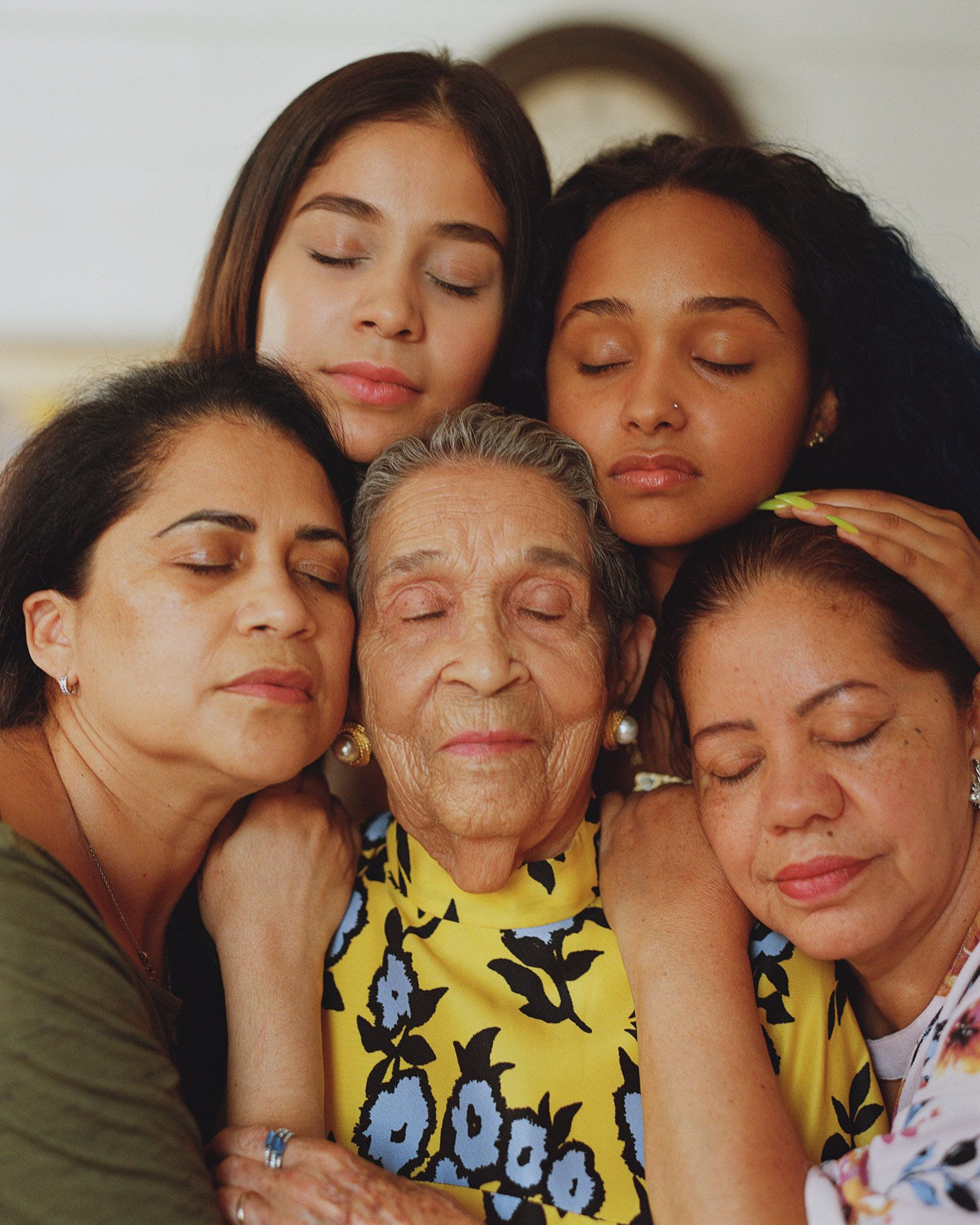 five generations of women posing together head against head around the oldest eyes closed by Oumayma B. Tanfous for Phosphenes Magazine