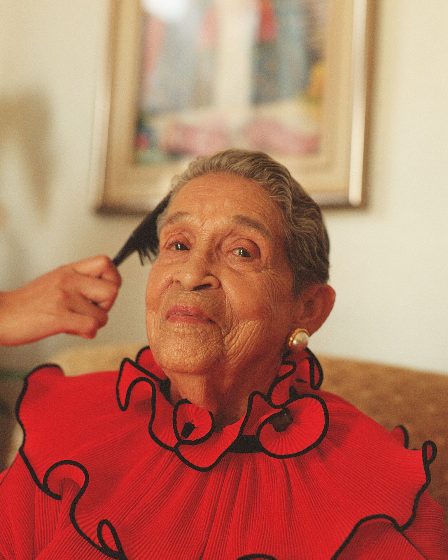 portrait of Altagracia de Pena getting her hair done by her granddaughter looking at camera smiling by Oumayma B. Tanfous for Phosphenes Magazine