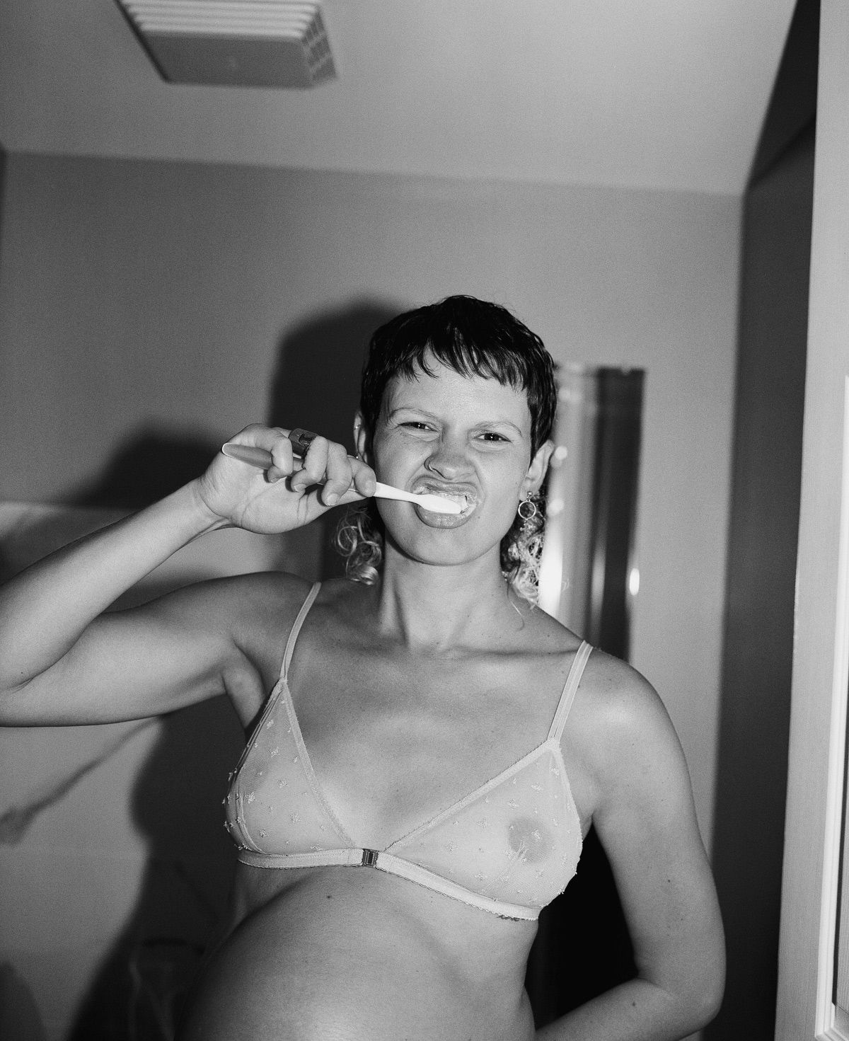 hair and makeup artist Valeria Amirova posing pregnant wearing ethically made clothes by Eliza Faulkner brushing her teeth in a bra photographed in black and white by Oumayma B Tanfous