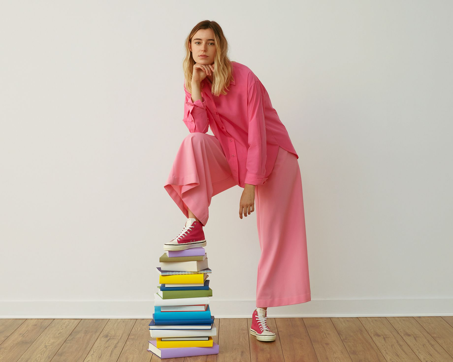 woman with pink pants posing on one leg
