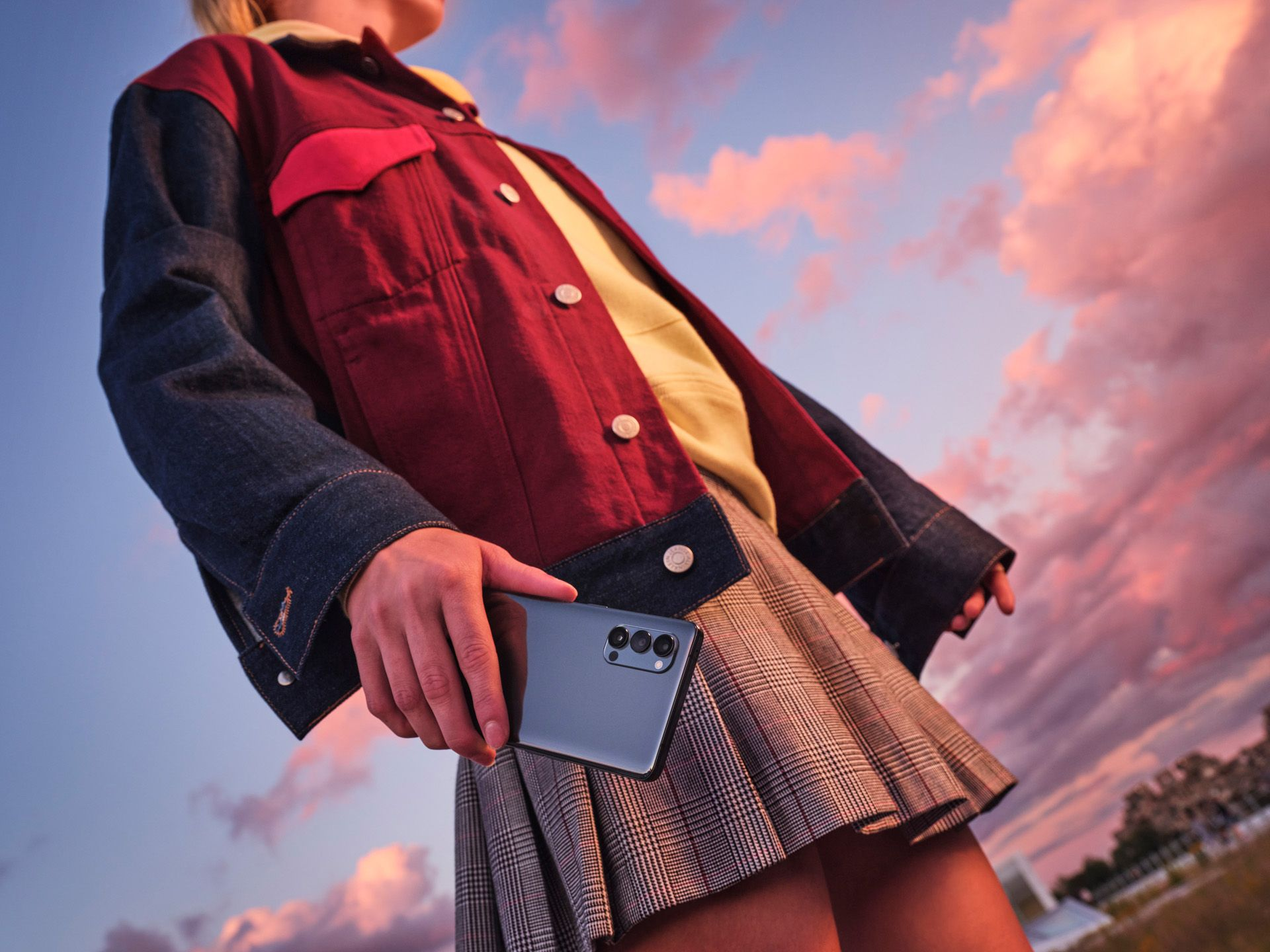 girl wearing a skirt with a oppo in the hands during sunset hour