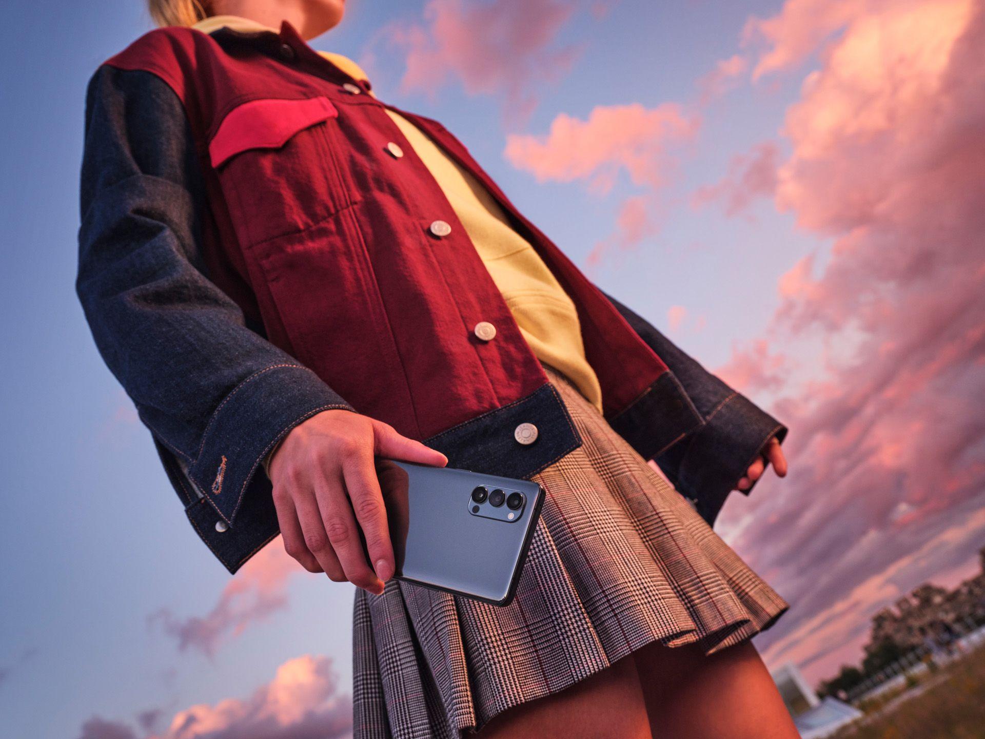 fille en jupe avec un telephone oppo dans les mains pendant le coucher du soleil