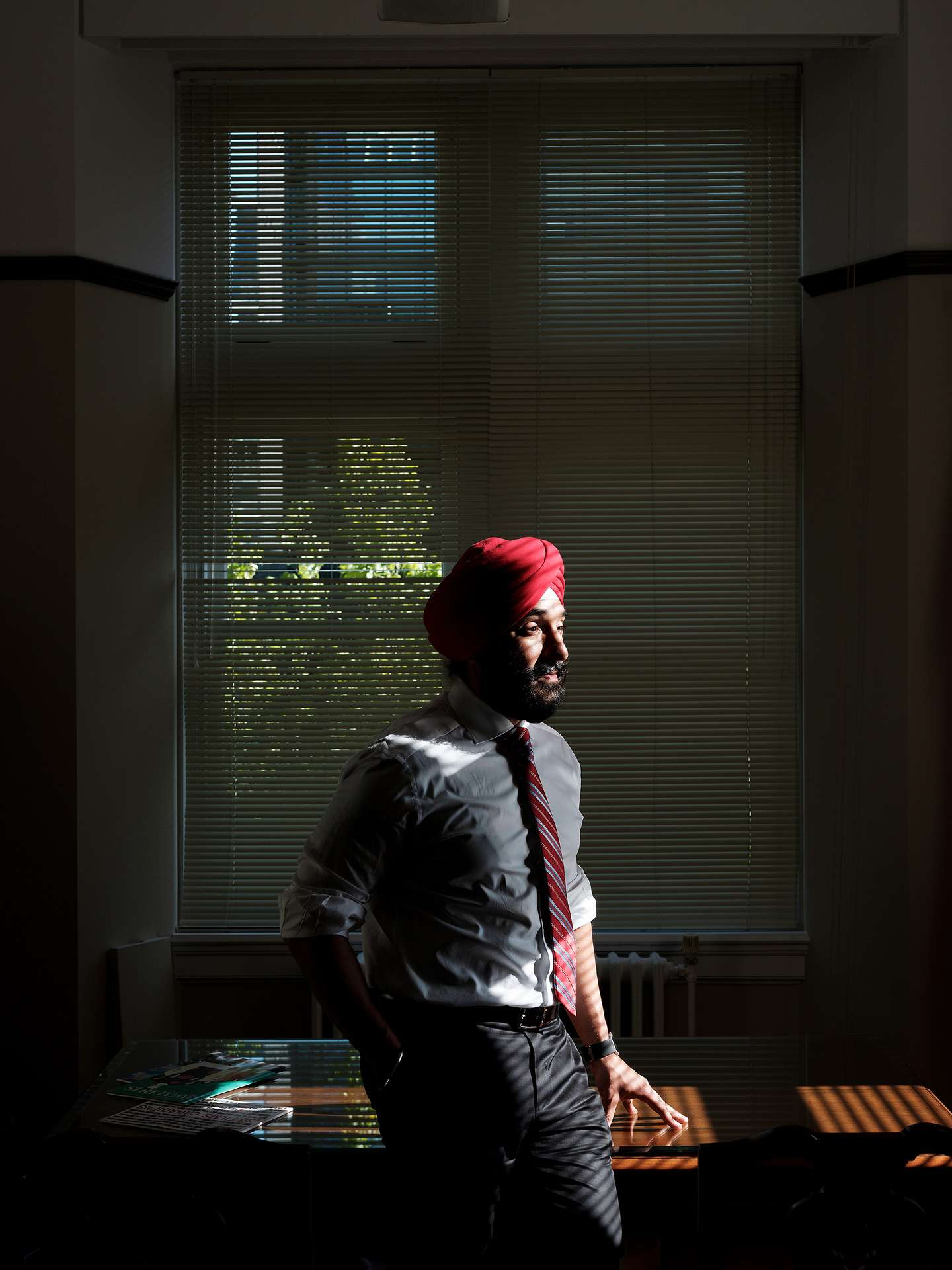 CPA Navdeep Bains in casual suit in his office in sunlight by Guillaume Simoneau for Pivot Magazine