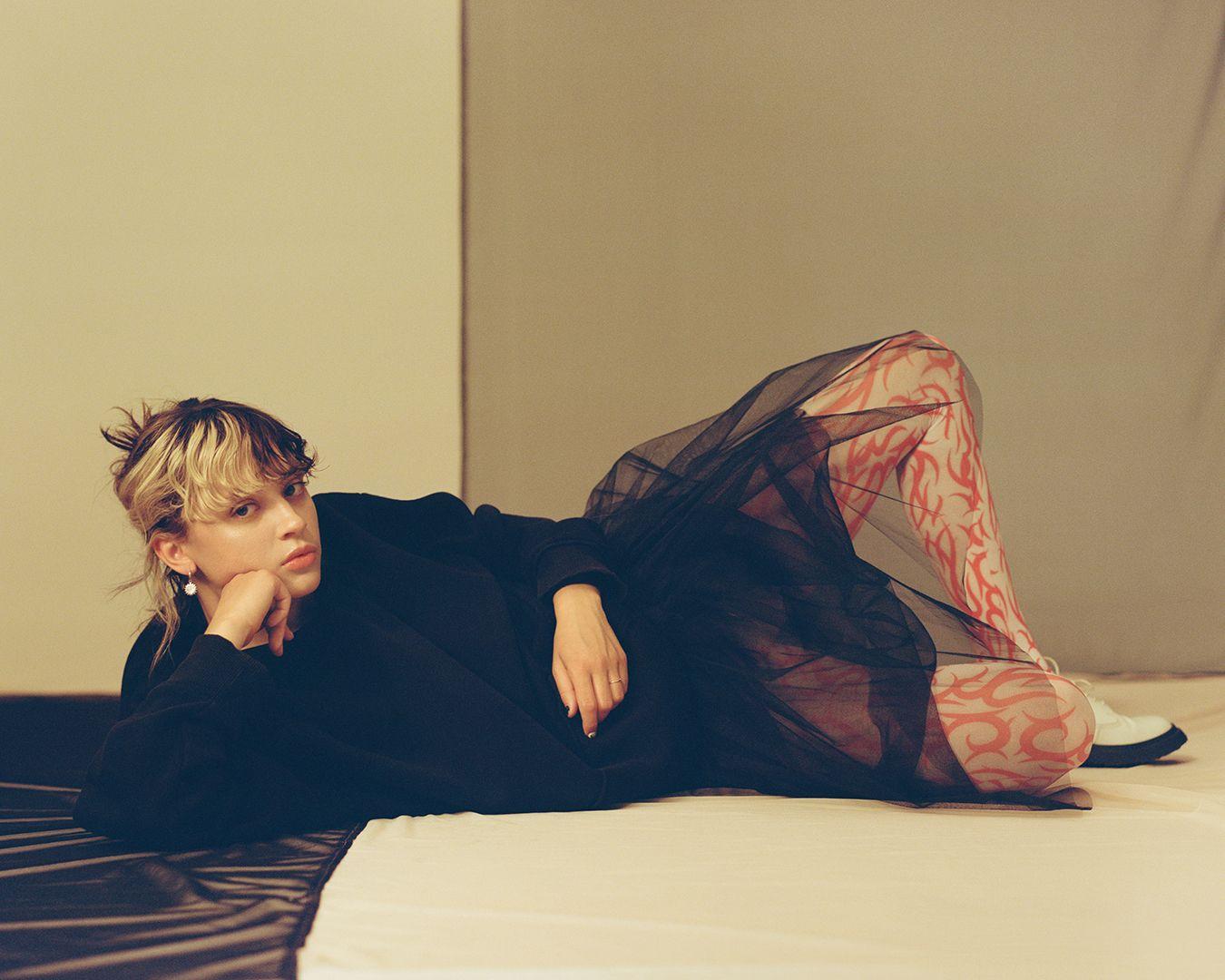 photo de l'artiste Pomme qui pose, couchée sur le sol