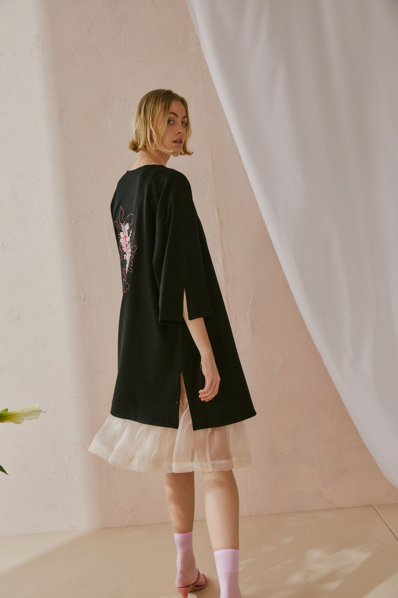 Une femme montre son dos mais tourne la tête vers la caméra. Elle porte un vêtement noir de type kimono avec une broderie de fleurs dans le dos. En dessous, elle porte une robe en organza beige avec des chaussettes et des sandales roses.