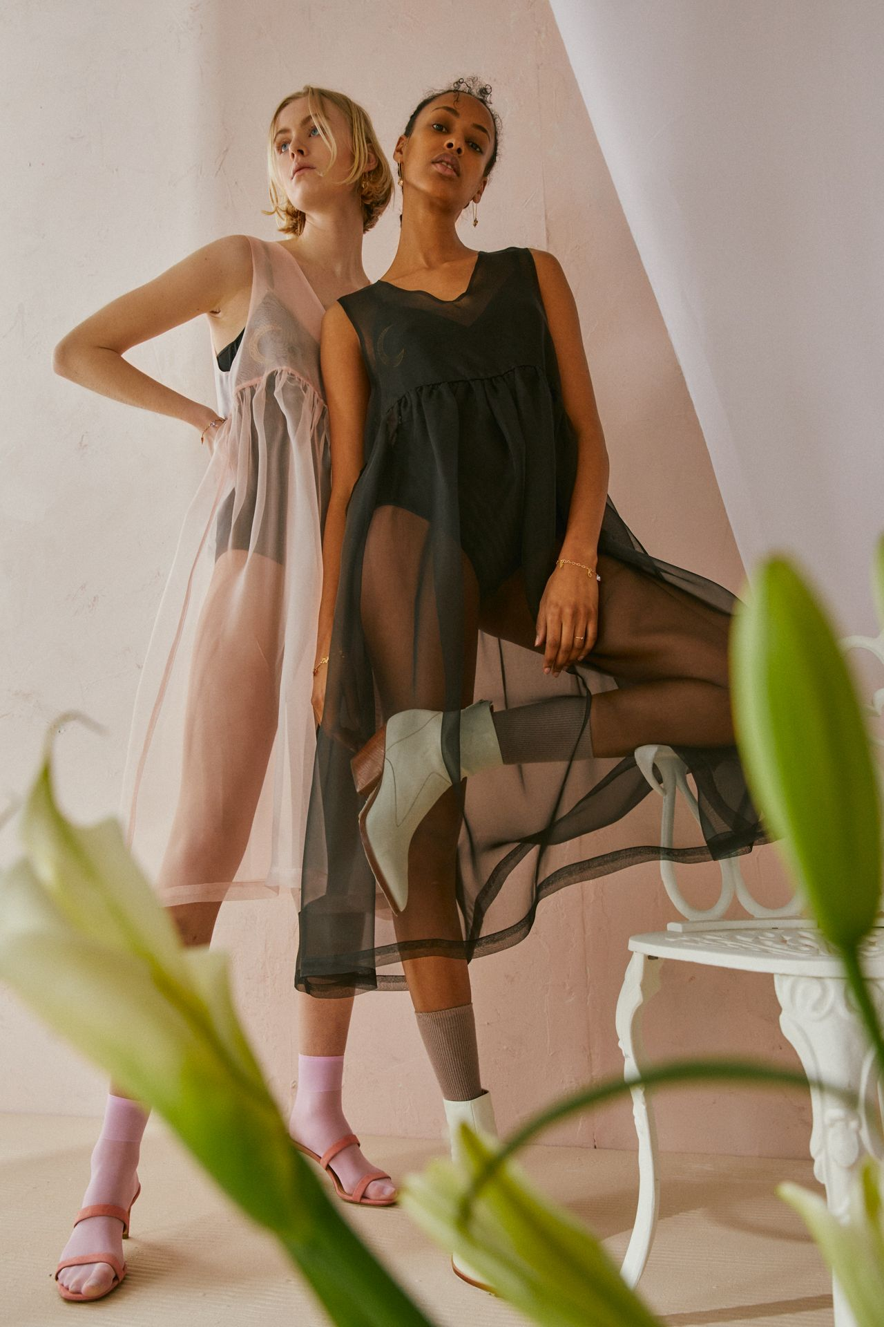 Deux femmes debout portant la même robe en organza à taille empire. L'une porte une version noire, l'autre une version rose.
