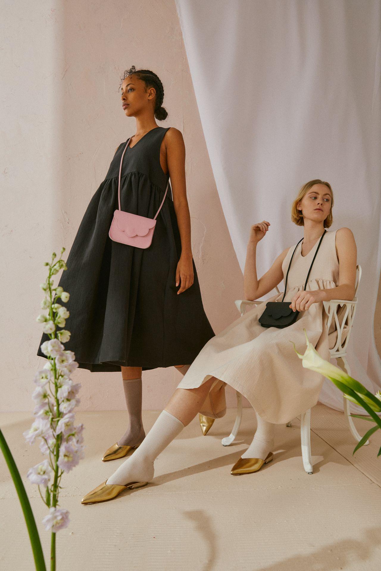 Une femme debout porte une robe noire sans manches à taille empire, des chaussures dorées et un sac à main rose. L'autre femme, assise sur une chaise, porte une robe beige sans manches à taille empire et un sac à main noir.