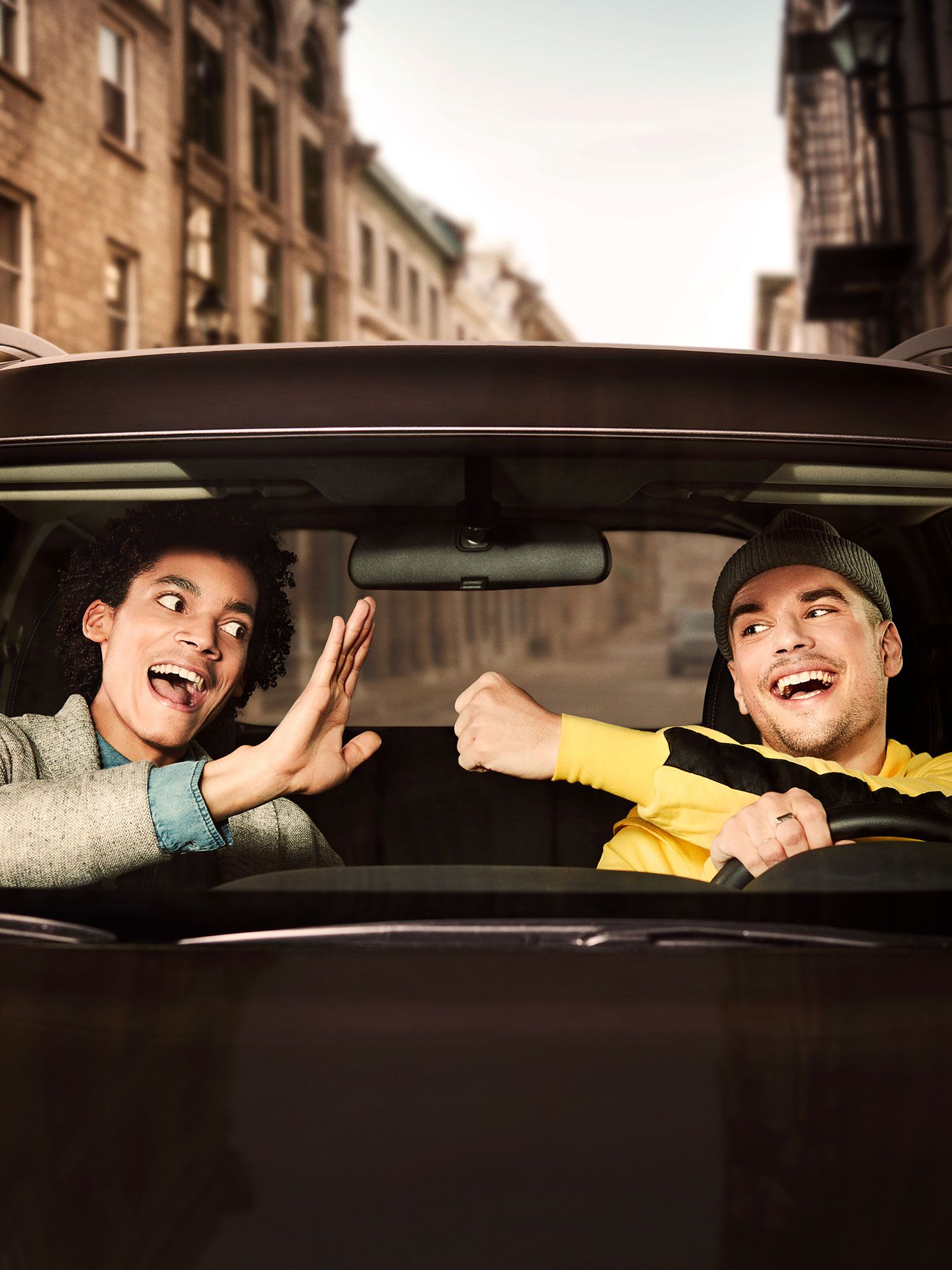 two young men in car one initiating a fist bump the other initiating a high five by Jocelyn Michel for Netlift