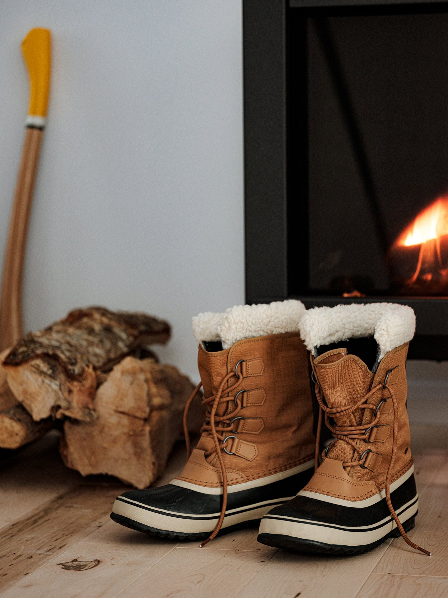 Sail sports gear photographed by Alexi Hobbs of camel-colored boots in front of fireplace