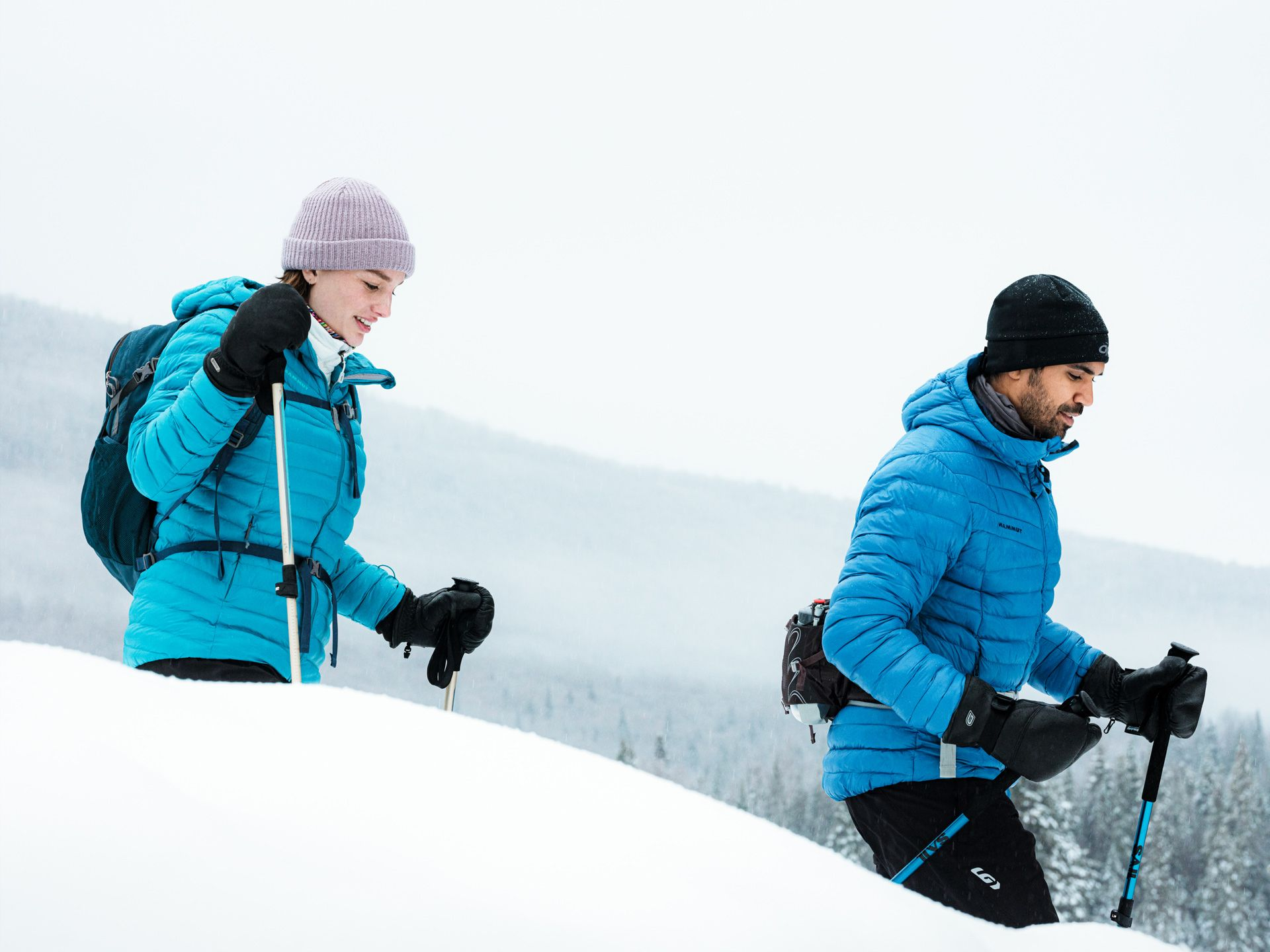 Sail sports gear photographed by Alexi Hobbs of two people treaking in nature in the snow both wearing bright blue jackets
