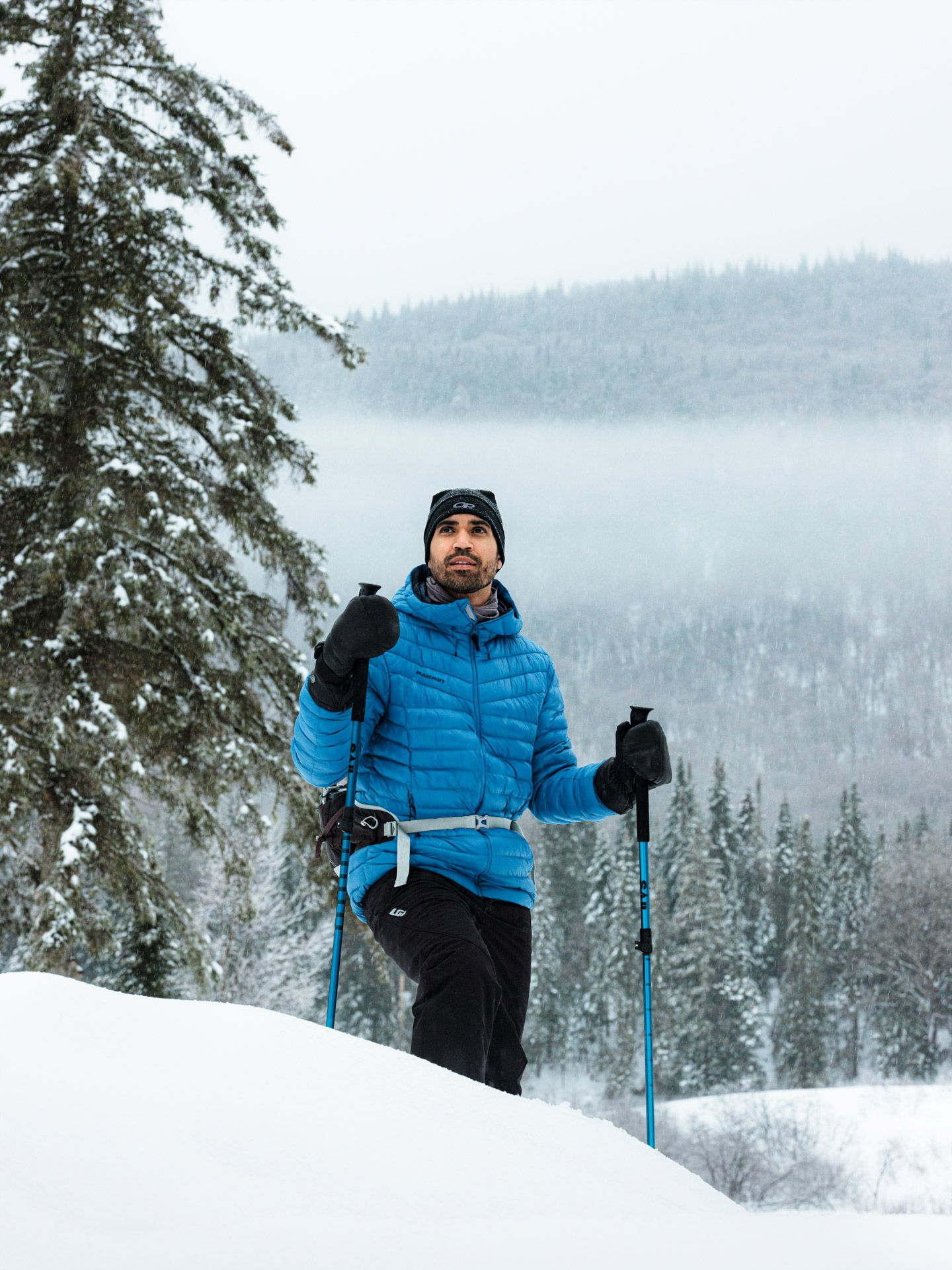 Sail sports gear photographed by Alexi Hobbs of man wearing bright blue jackets treaking in nature in the snow