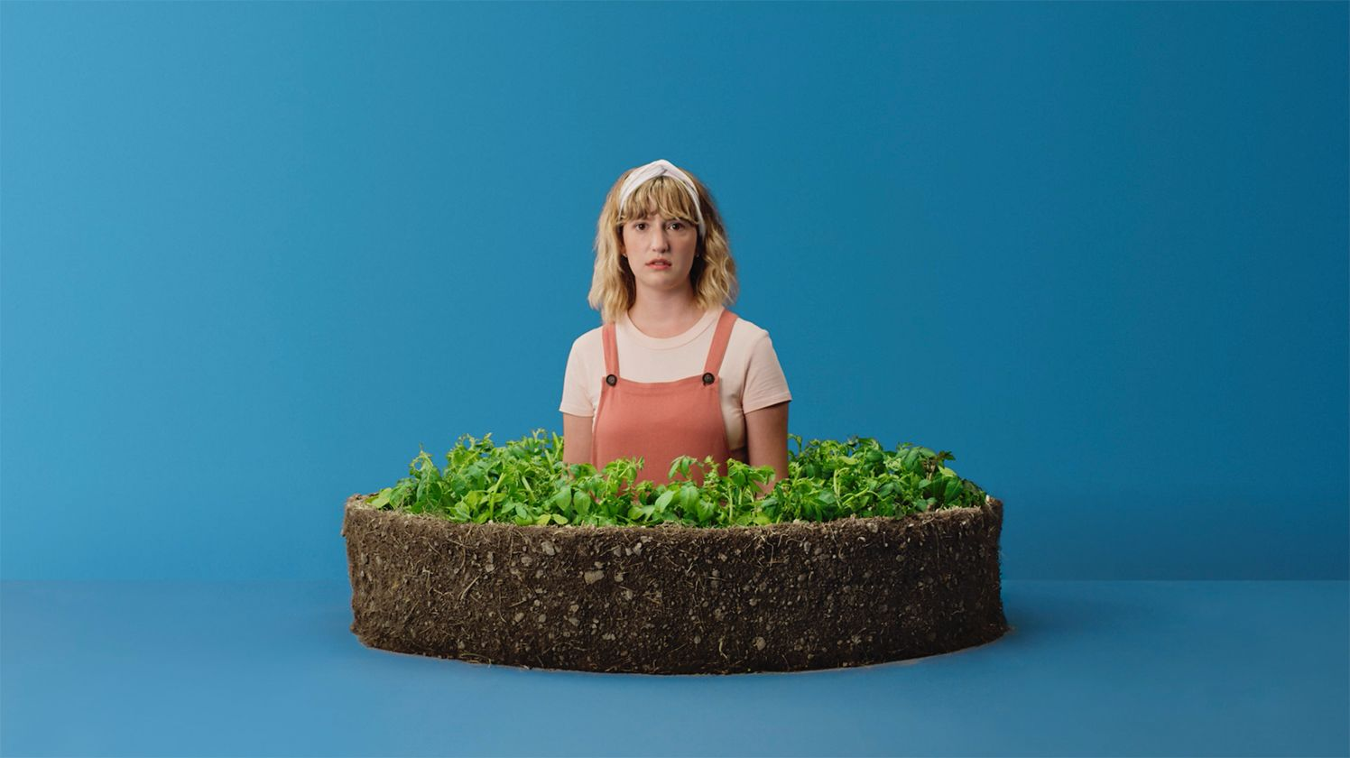 Photo d'une fille qui parle de patates devant un fond bleu.