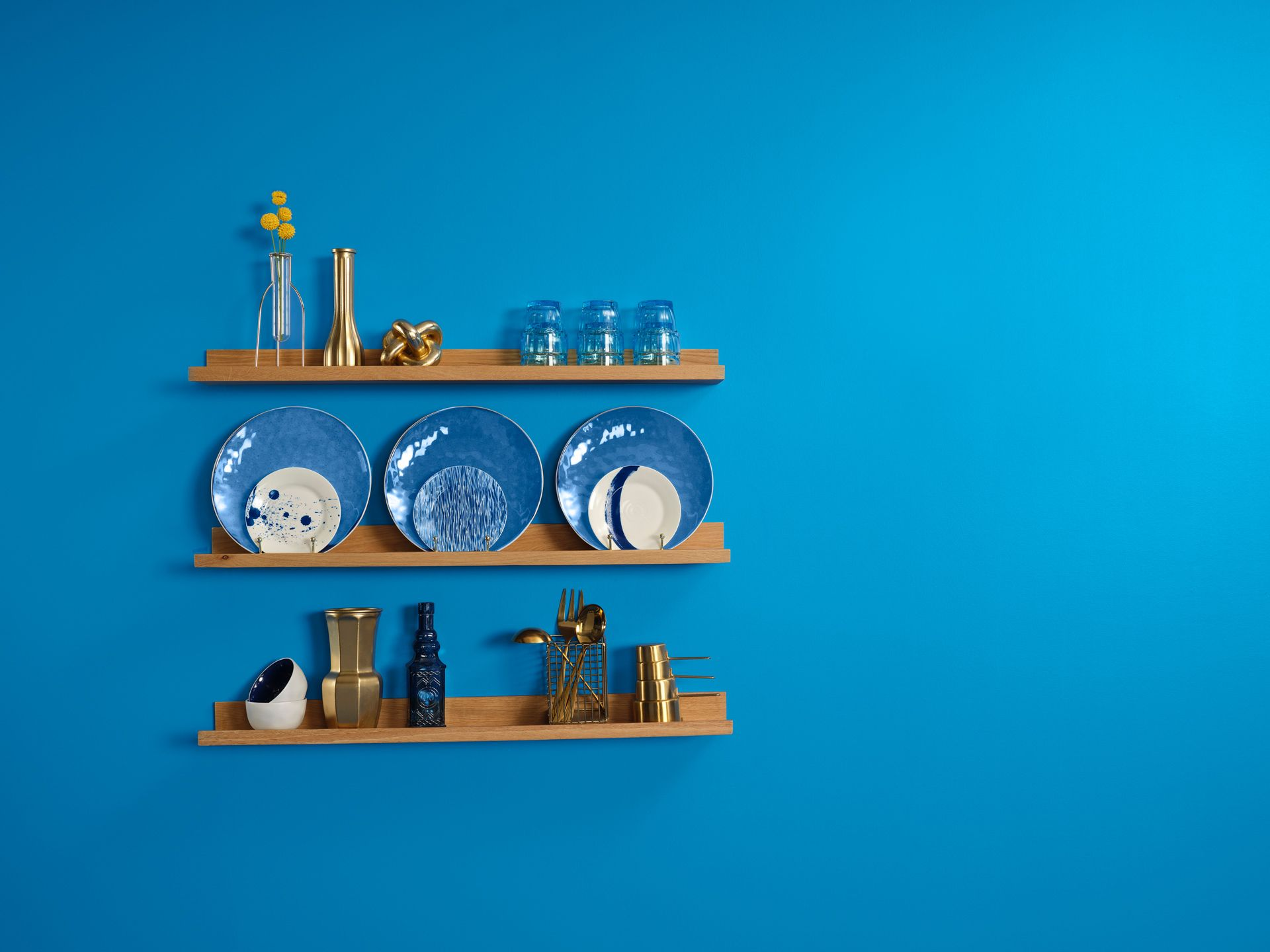 Blue wall with wood shelves and gold or blue kitchen objects on them.