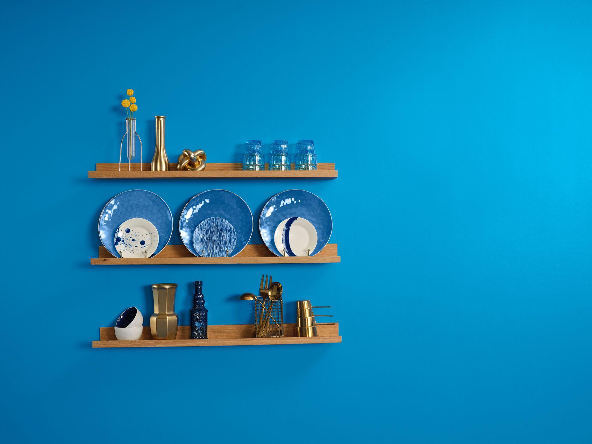Mur bleu avec des étagères en bois sur lesquelles sont posées des objets de cuisine bleus ou dorés.