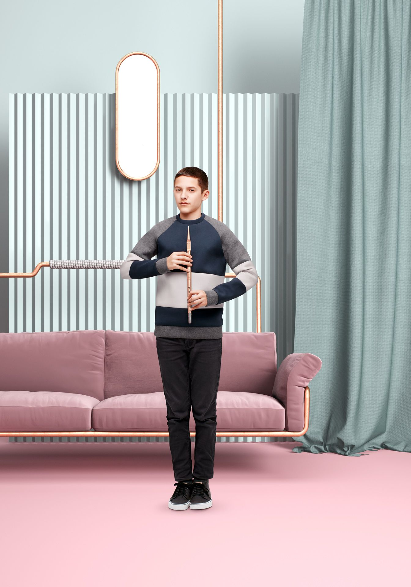 young boy holding flute with two hands looking at camera in front of pink couch held by copper pipes textured background and dark turquoise drapes by Simon Duhamel for Bloom Maestro