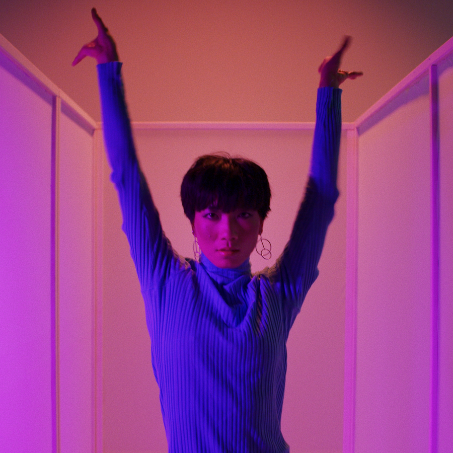asian dancer arms in the air looking at camera in blue lighting on pink background for Fabrikate by Simon Duhamel