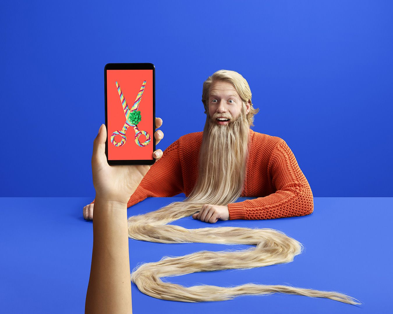 montage surréaliste d'un homme avec une très longue barbe et une main tenant un téléphone mobile affichant une paire de ciseaux par Simon Duhamel pour Fizz