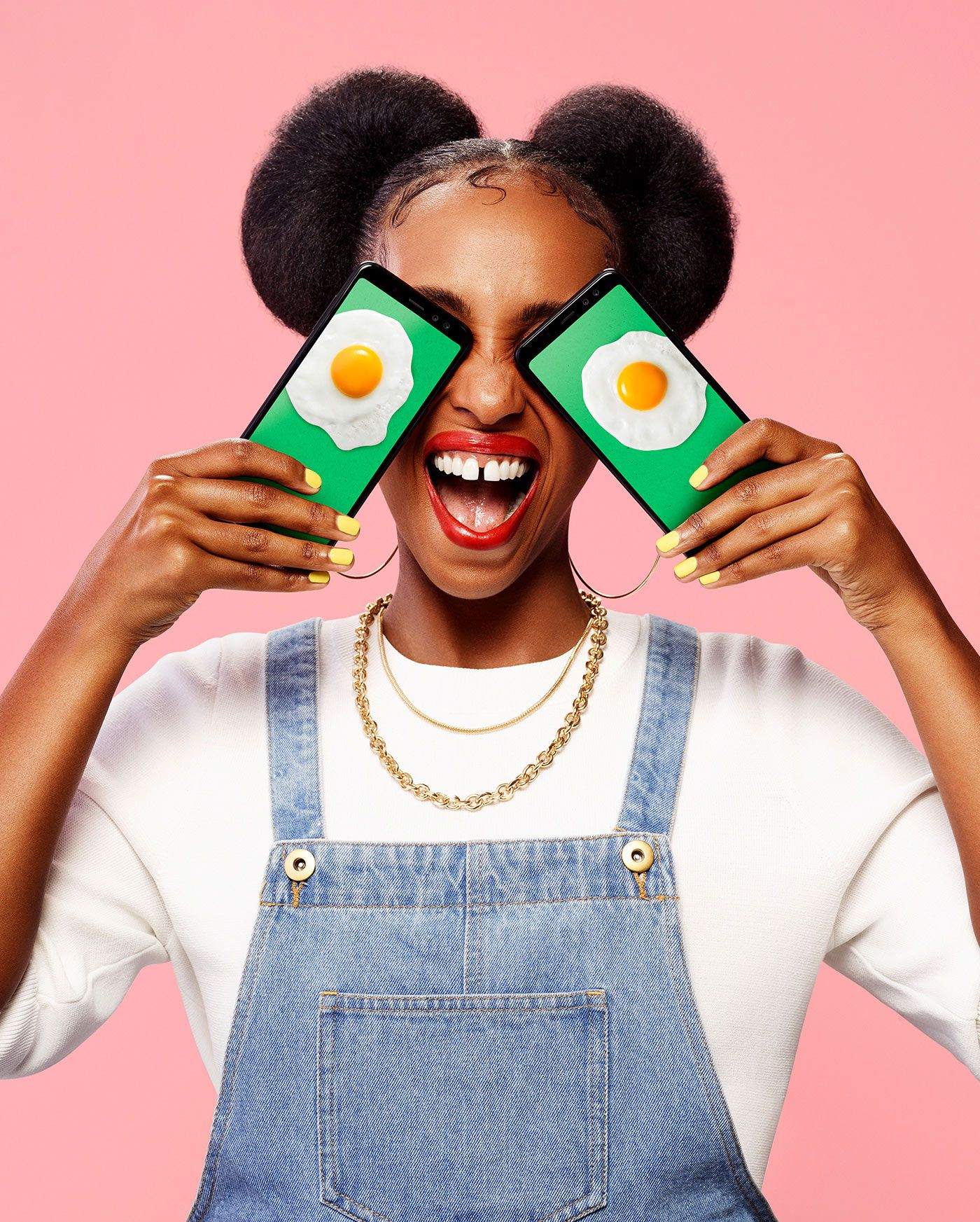 black woman wearing jeans overall and white shirt on pink background with big smile holding two telephones over her eyes displaying pictures of sunny side up eggs by Simon Duhamel for Fizz brand launch with Ogilvy