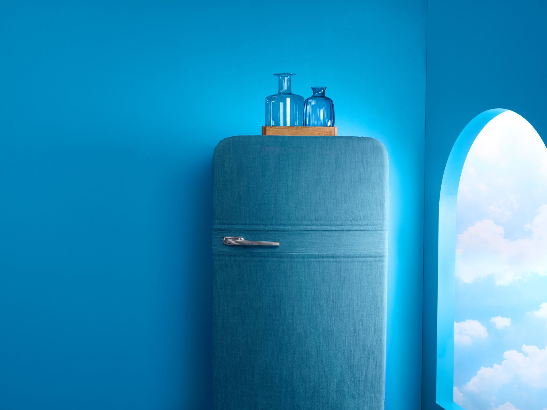 Blue room with a blue fridge and fake looking blue sky through a rounded window.