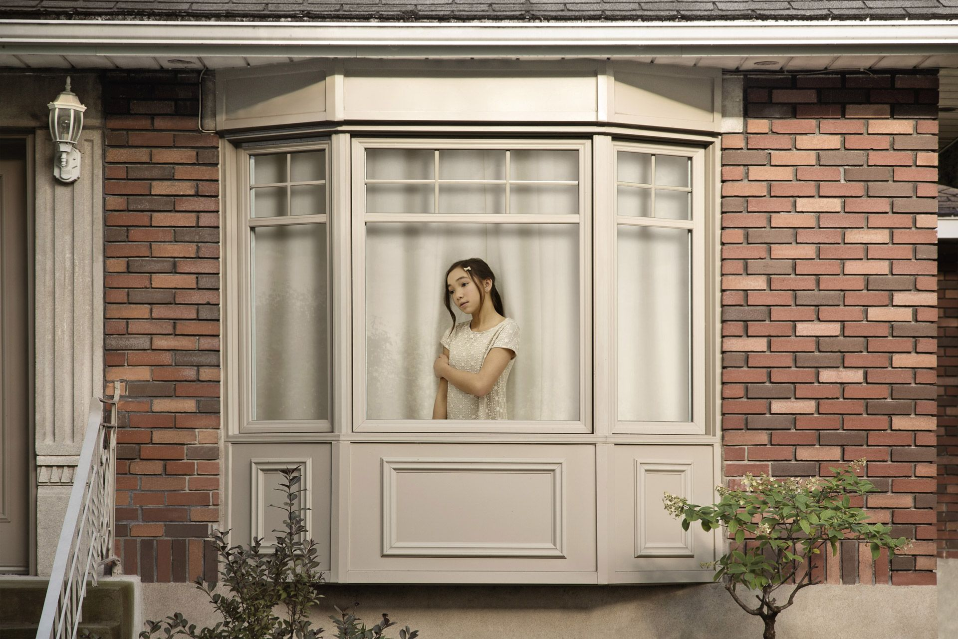 young asian girl dressed in white inside house looking sadly out the window by Simon Duhamel for In Between