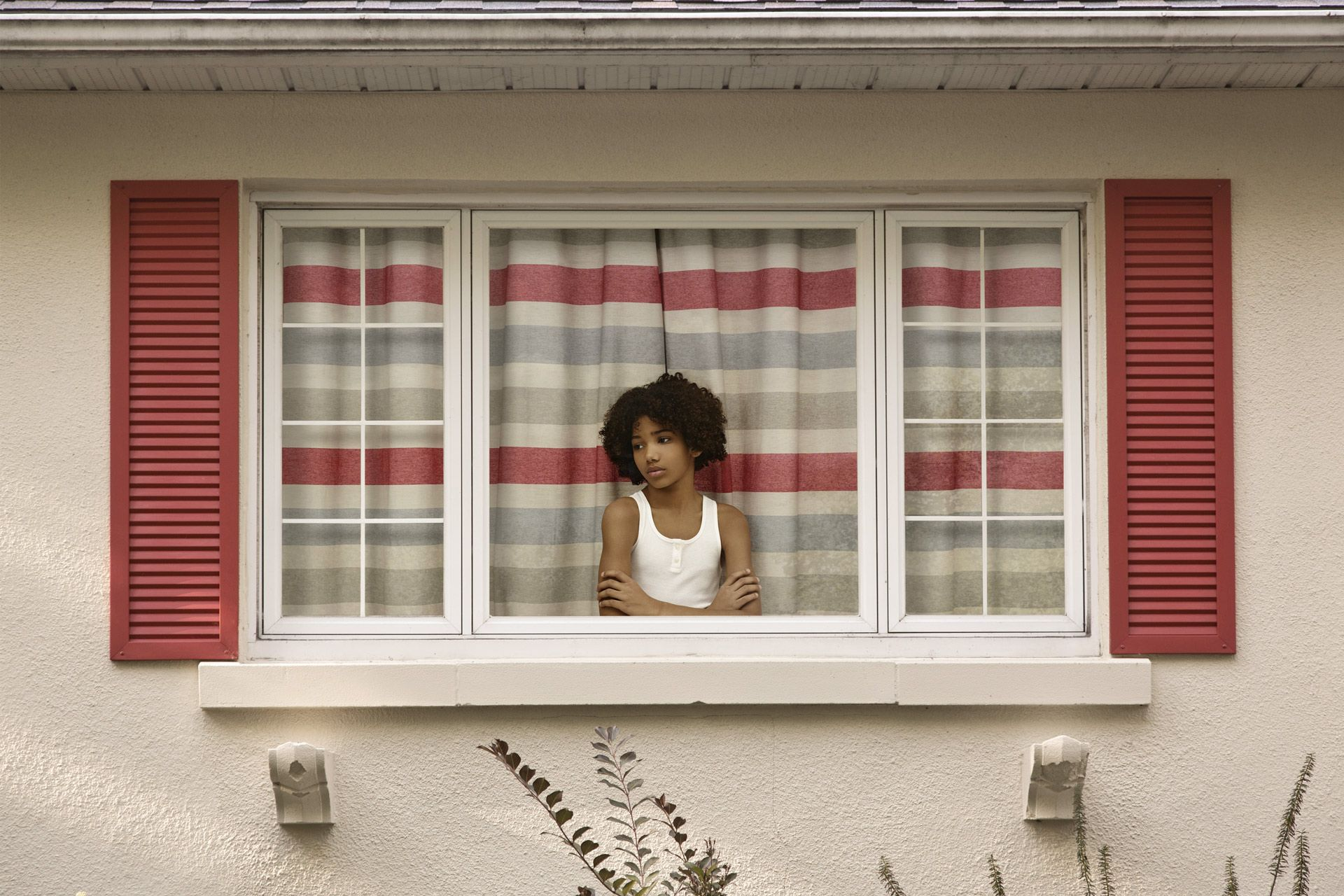 young black boy with white shirt inside house looking sadly out the window by Simon Duhamel for In Between